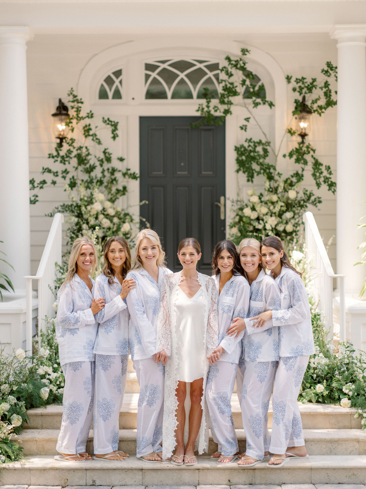bridesmaids wearing matching blue and white pj sets with bride in white pjs