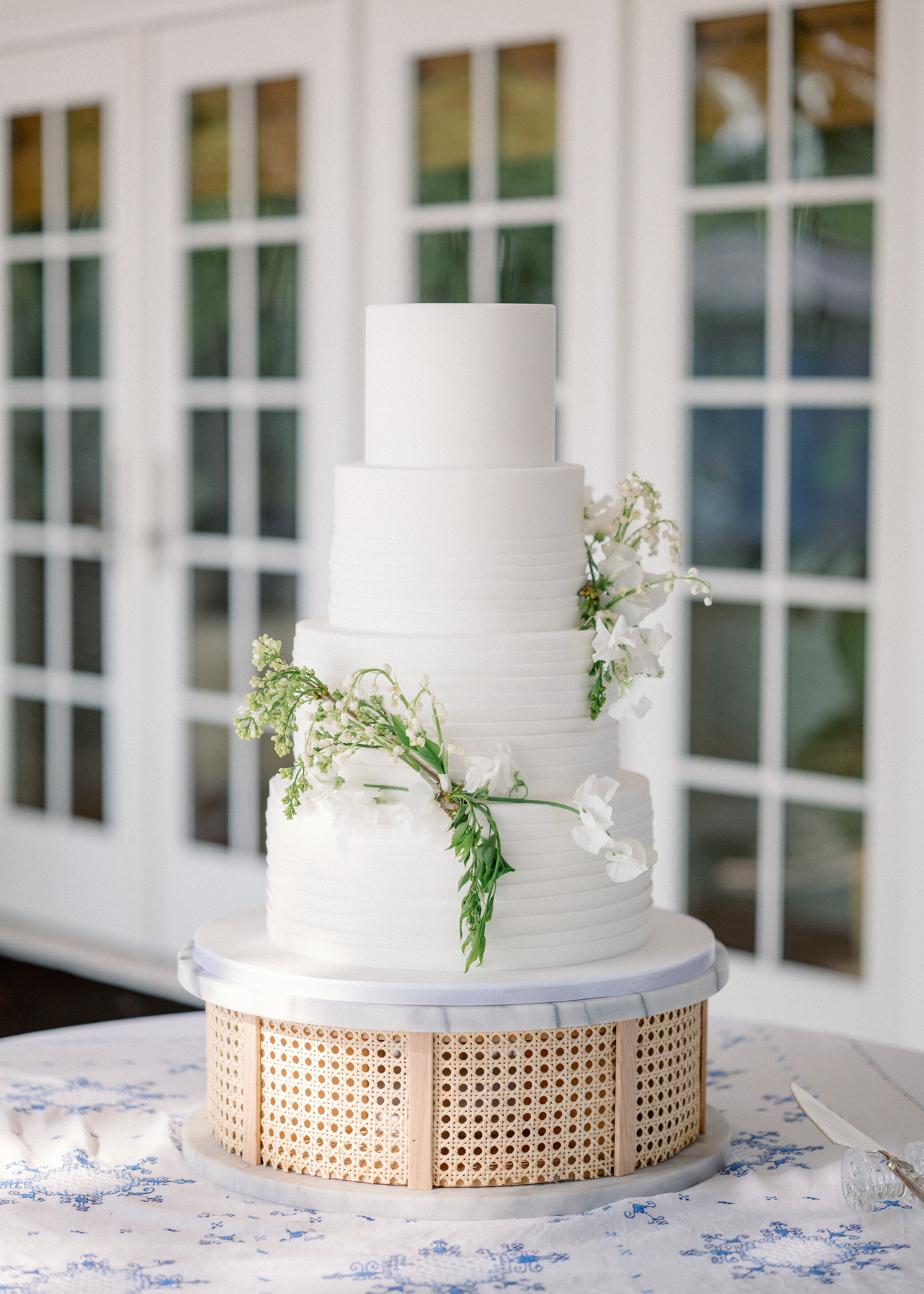 four tiered white frosted wedding cake with white lily of the valley floral decor