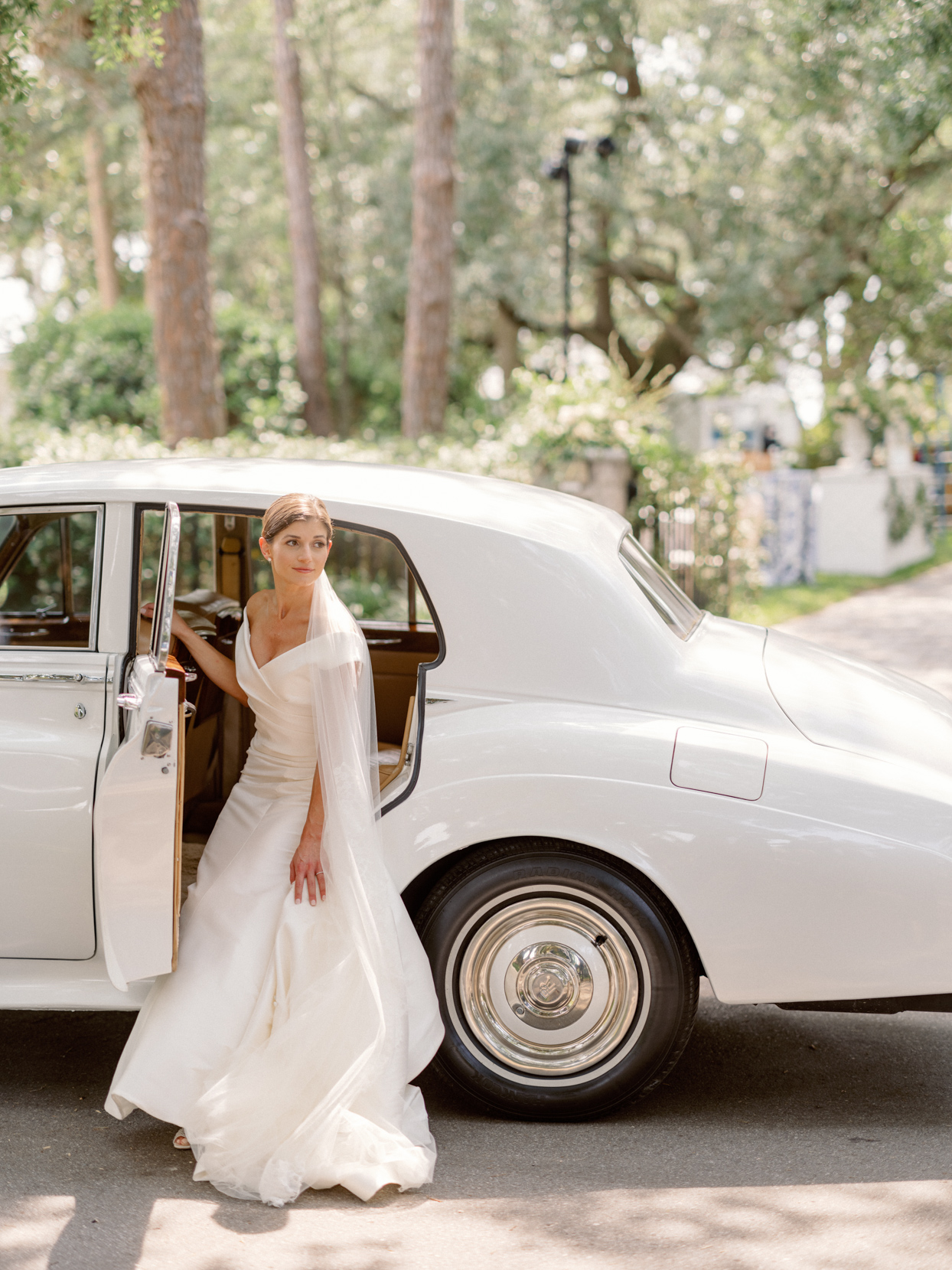 bride getting out of white vintage car