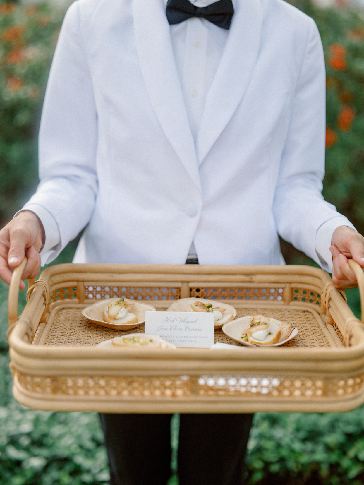 black and white tux server holding wicker serving tray with appetizers