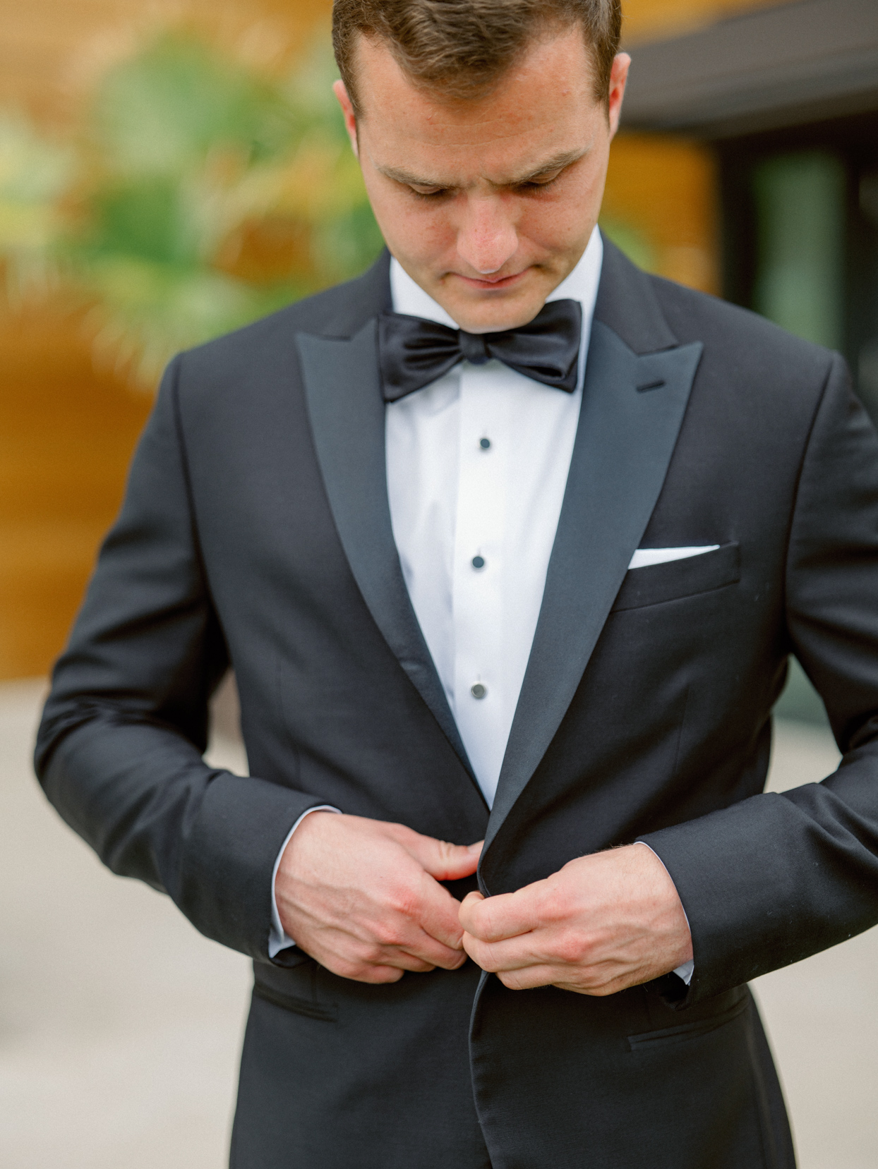 groom wearing formal black and white tux