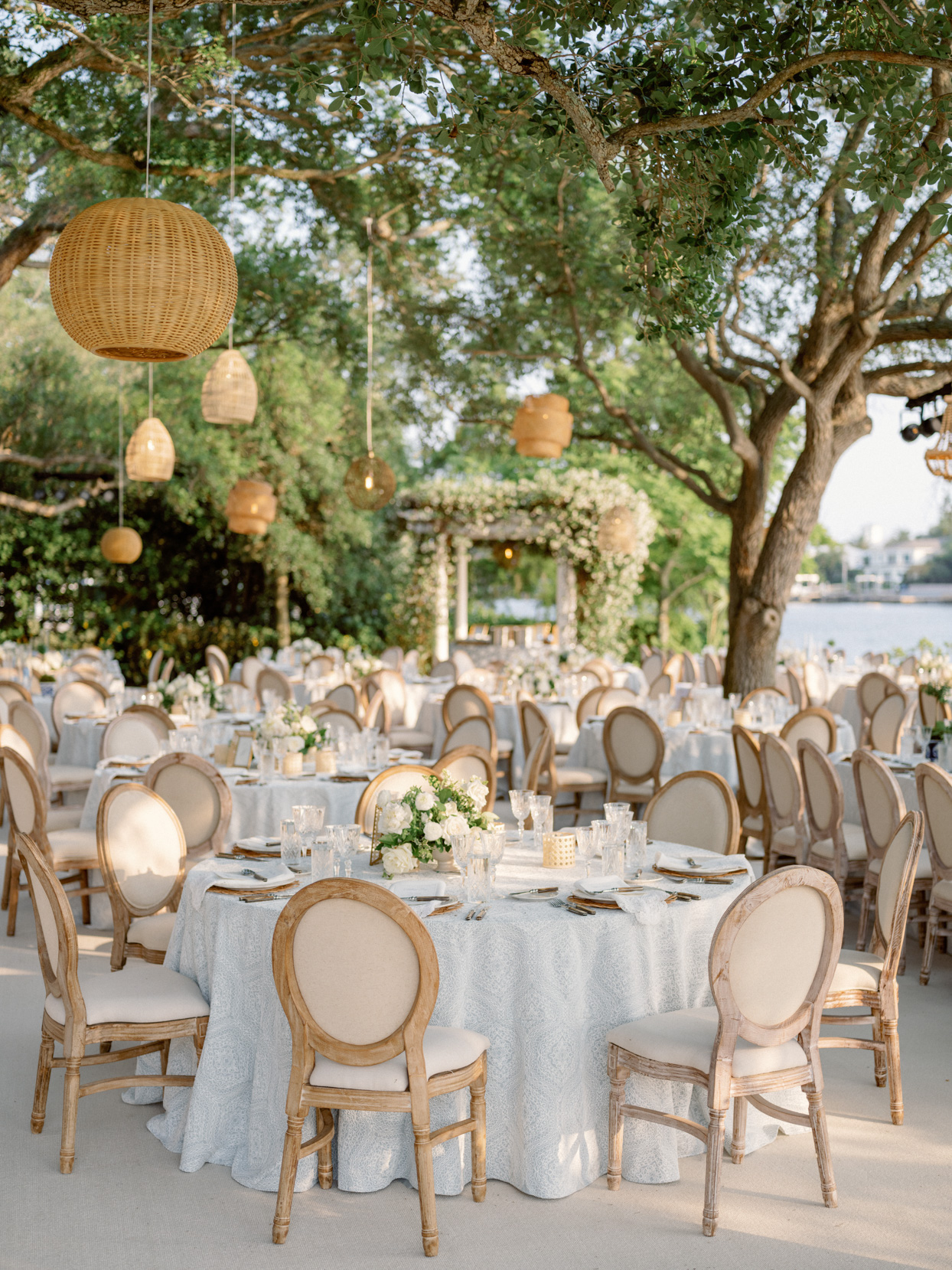 wicker lanterns hanging over round blue and white linen draped tables