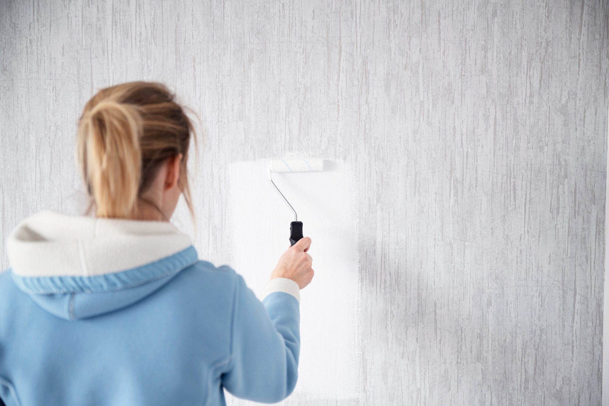 woman painting over wallpaper