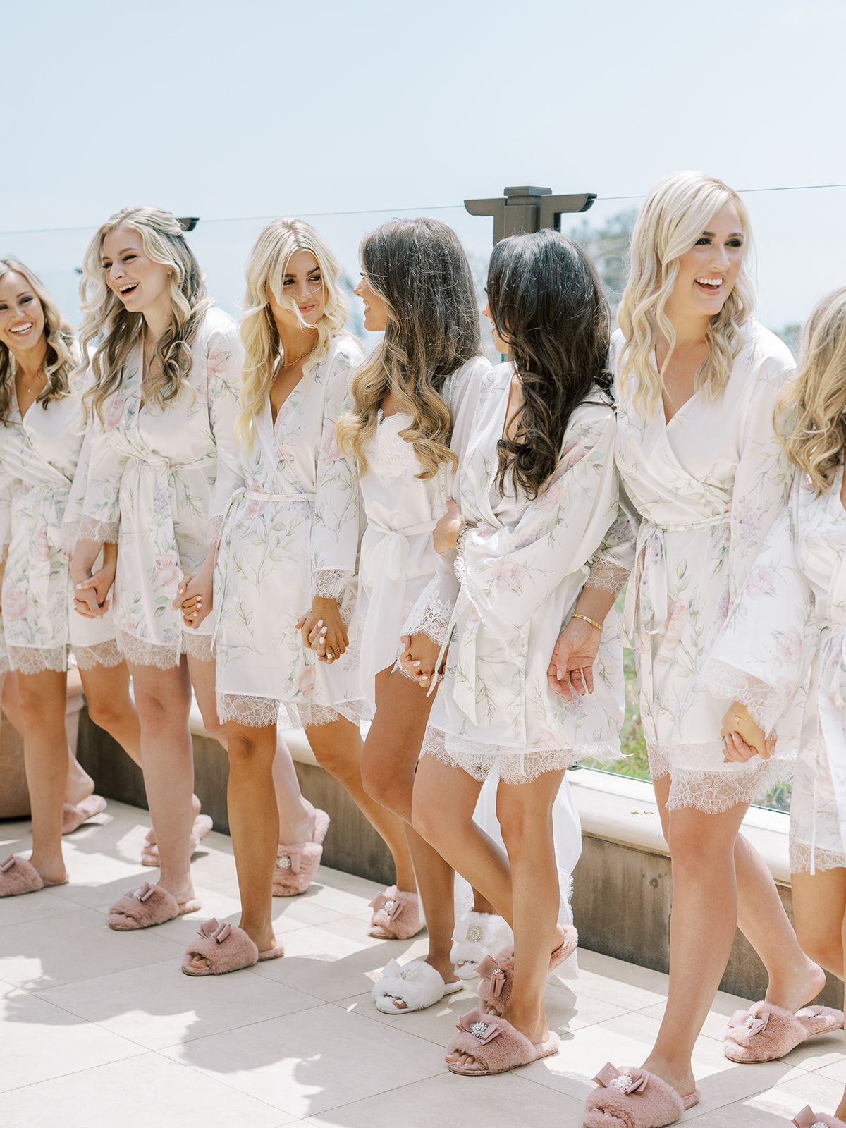 bridesmaids in matching white patterned robes walking hand in hand