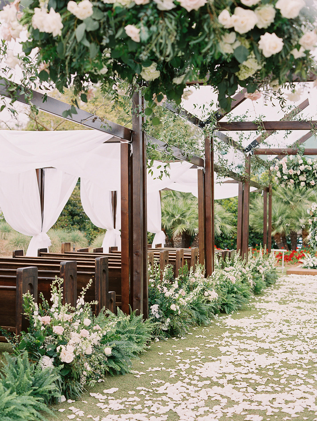 outdoor ceremony with wooden pews and flower petals in aisle
