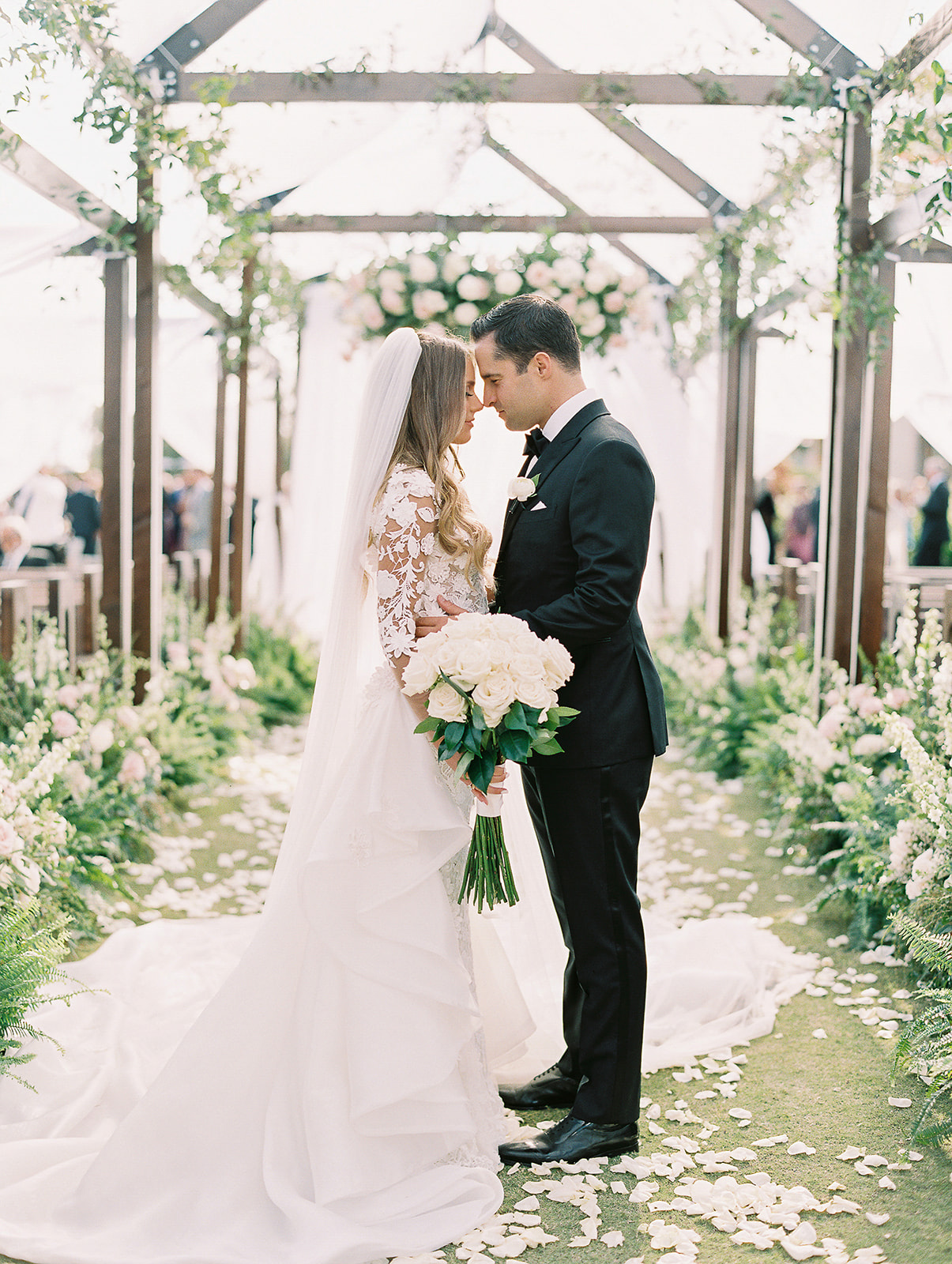 couple portrait in wedding ceremony aisle with flower petals on the ground
