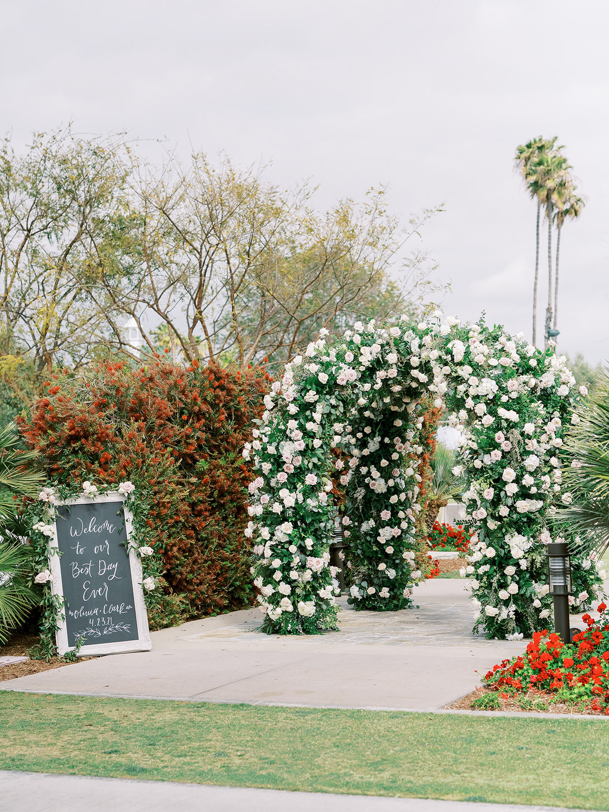 large rose arches at wedding entrance