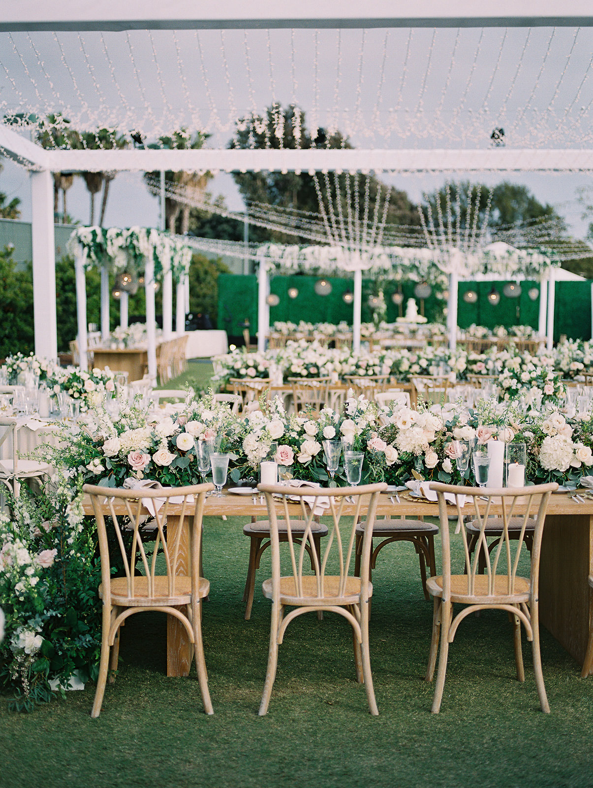 long floral garlands on wooden outdoor wedding reception tables