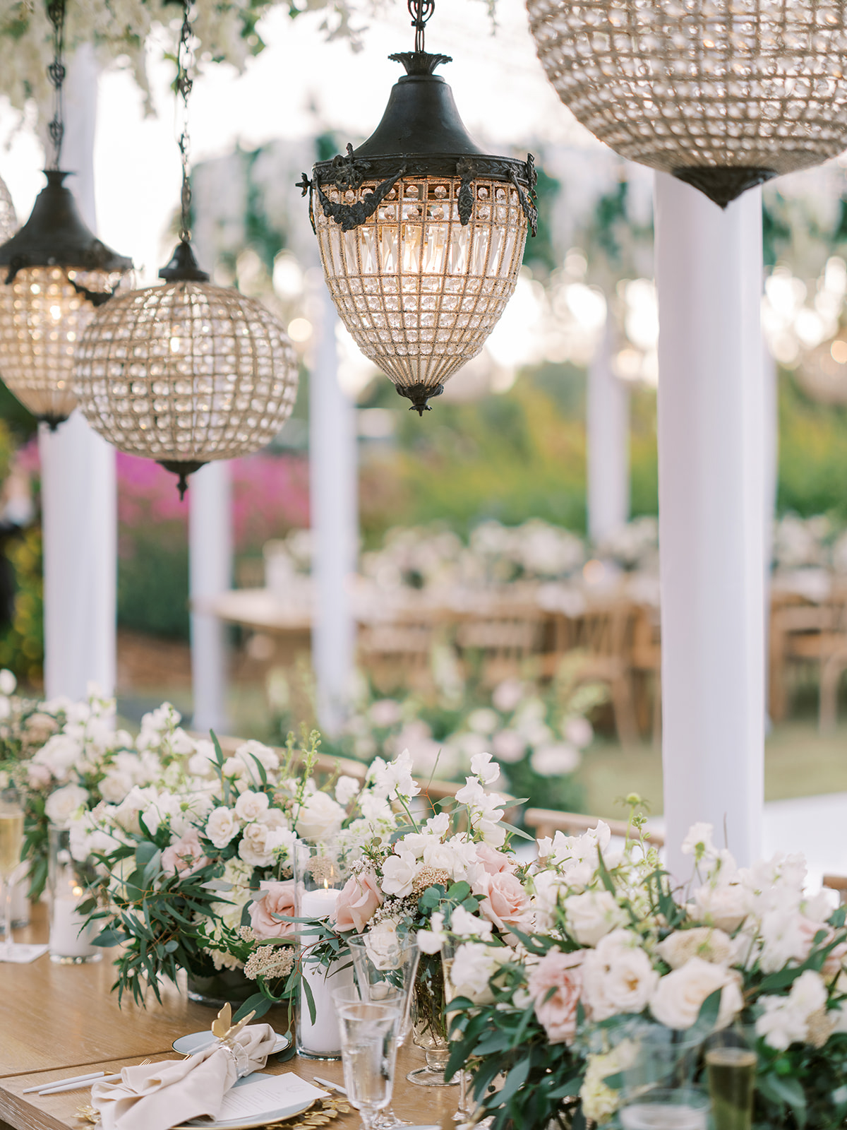 elegant lanterns hanging above wedding reception table with pink and white flowers
