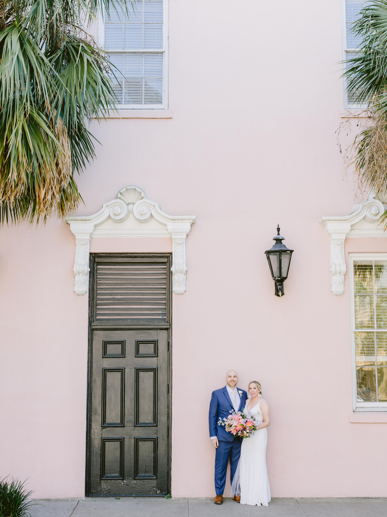 bride and groom posing in front of pink building