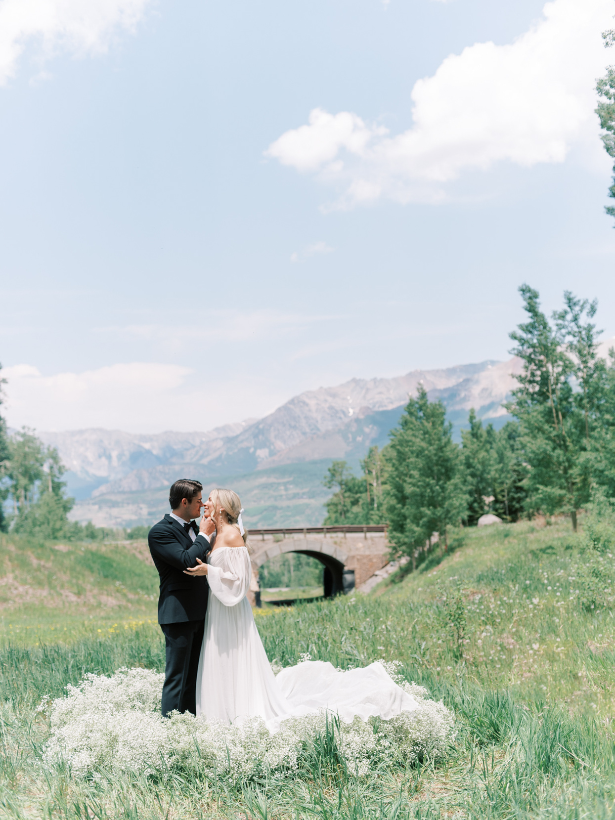 bride and groom near bridge and mountains