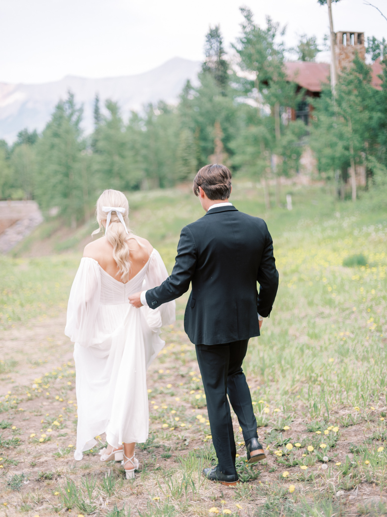 bride and groom walking in grass