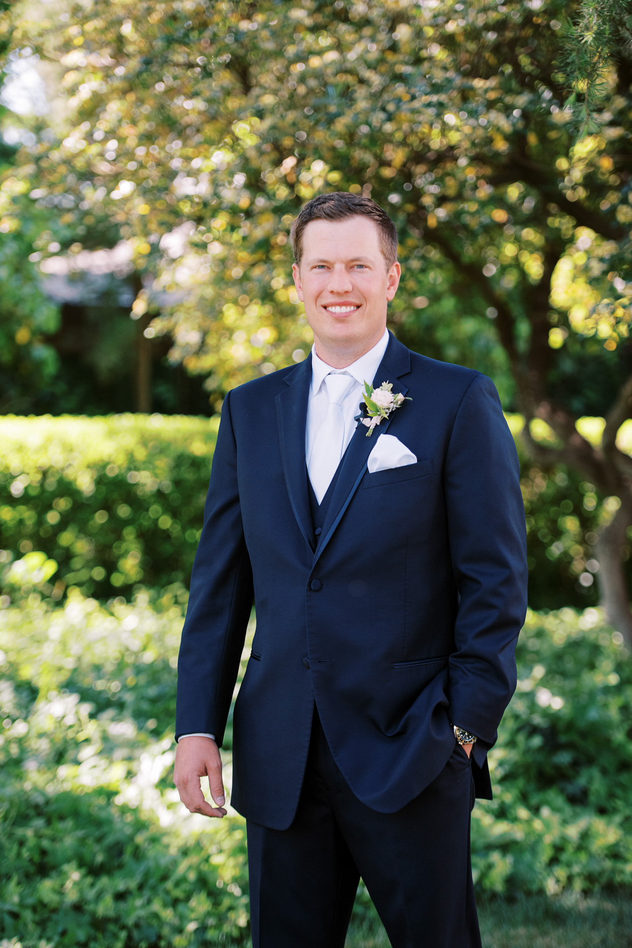 groom in navy suit with floral boutonniere
