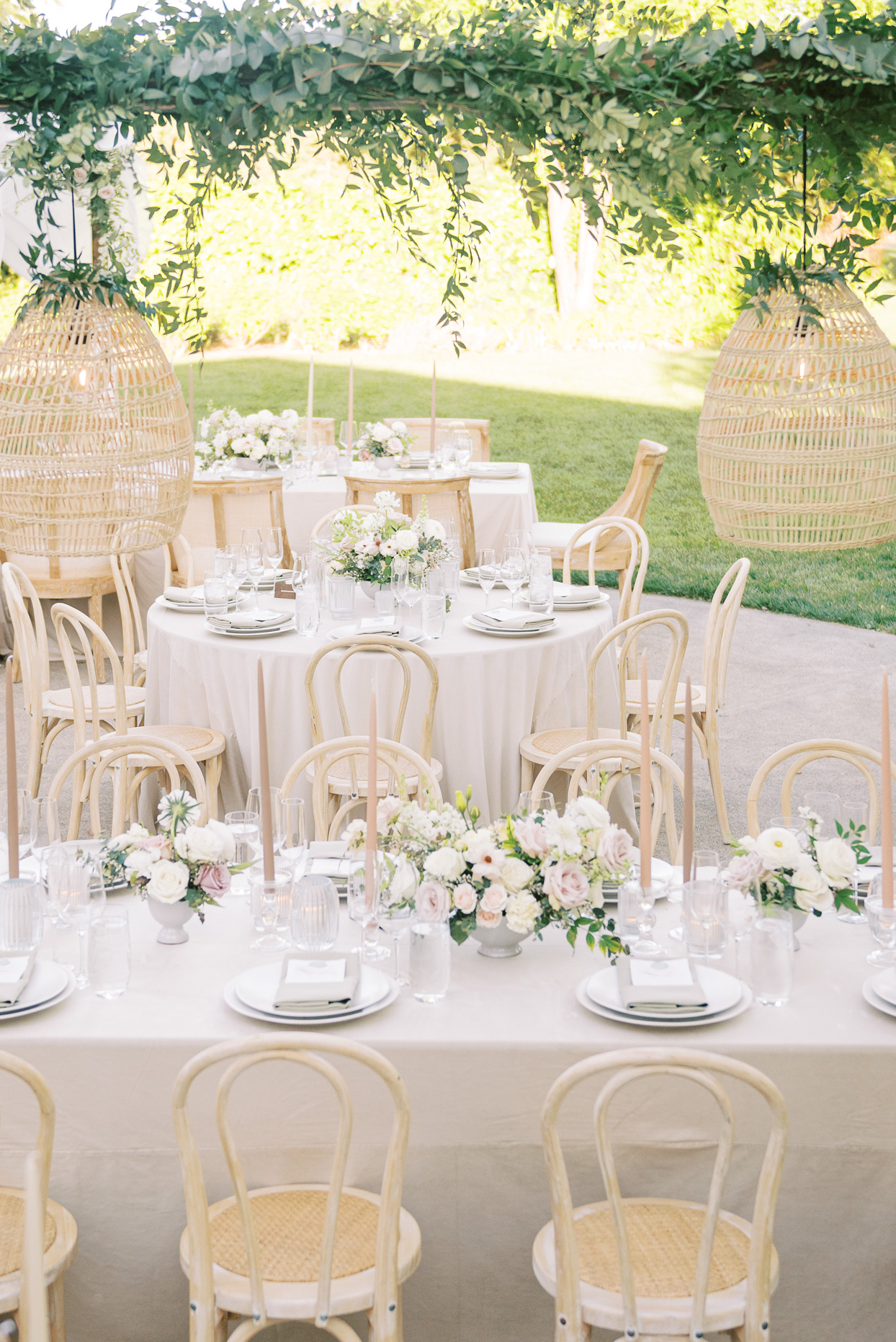 reception tables with floral accents and rattan chairs