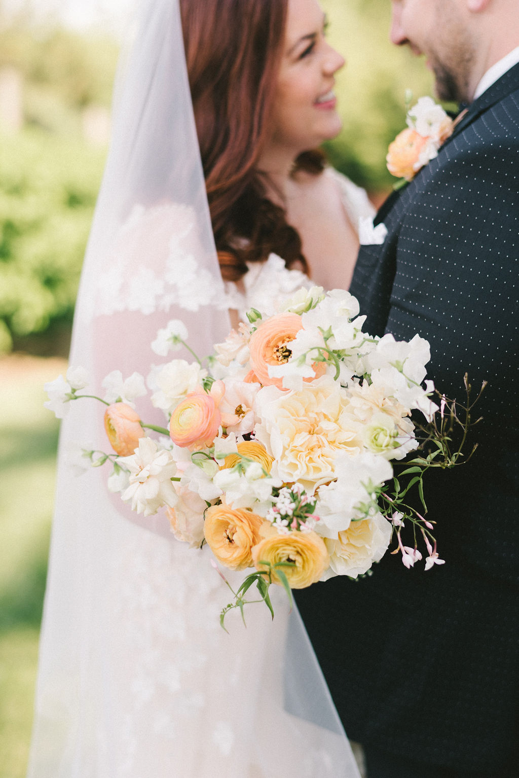 bride and groom with white, orange, and peach wedding bouquet