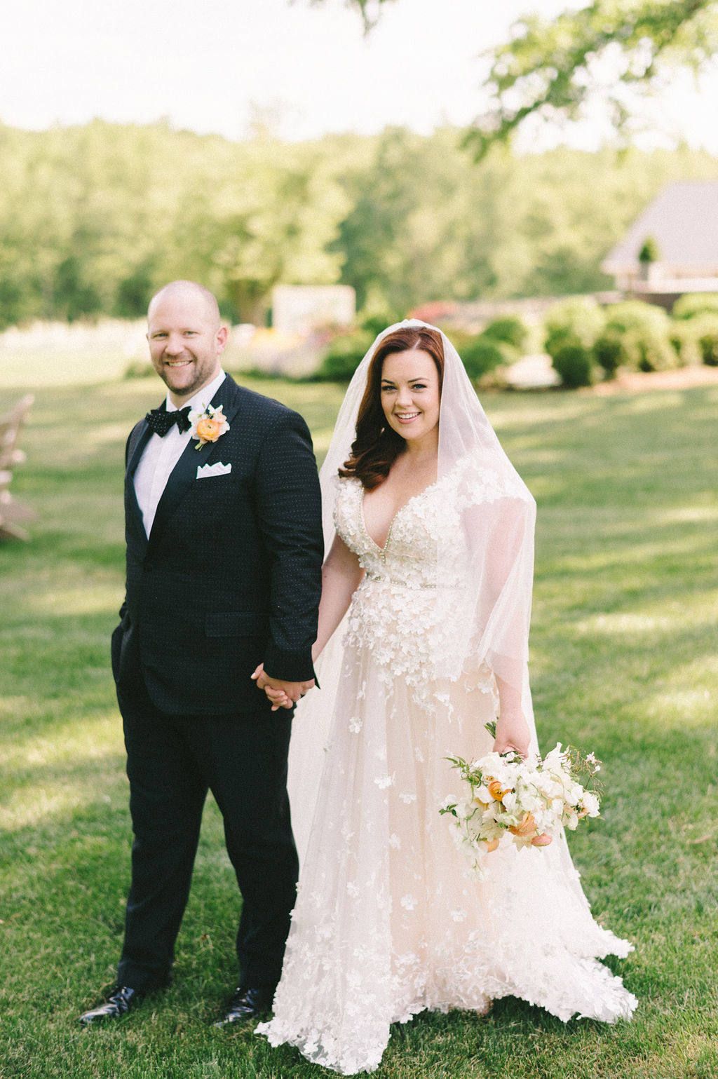 bride and groom holding hands for portrait on lawn