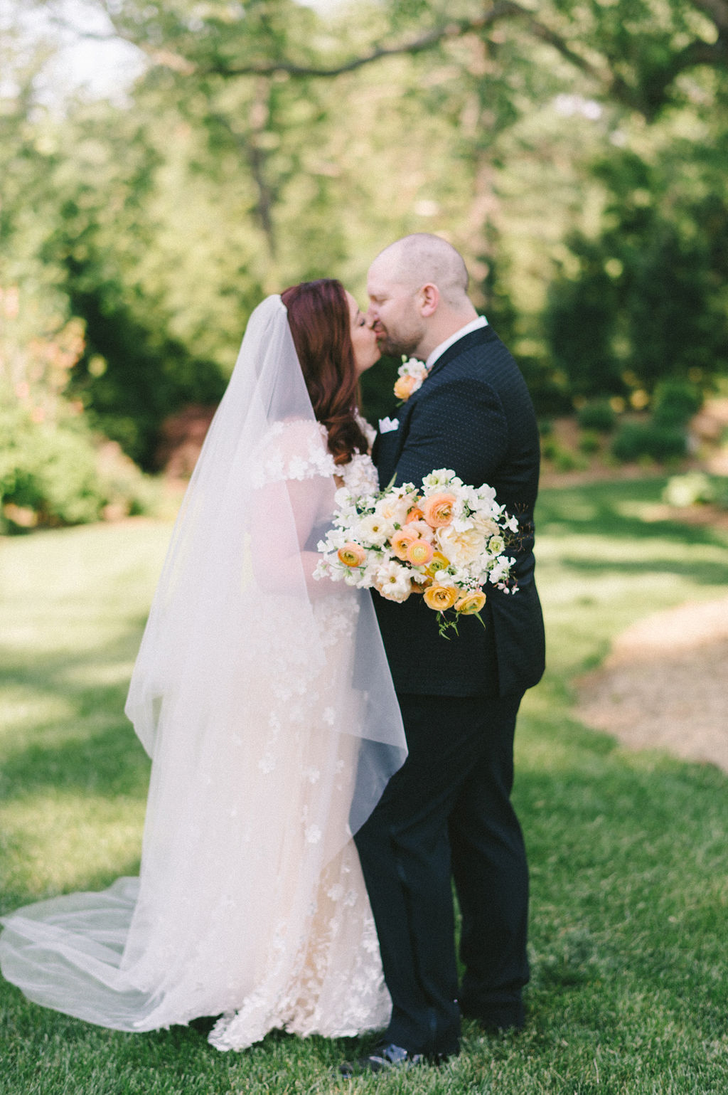 wedding couple kissing for portrait on lawn