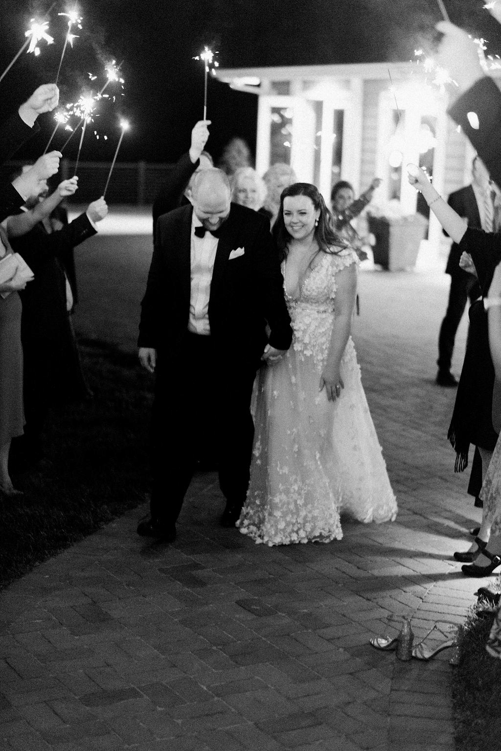 bride and groom exit wedding while guests hold sparklers