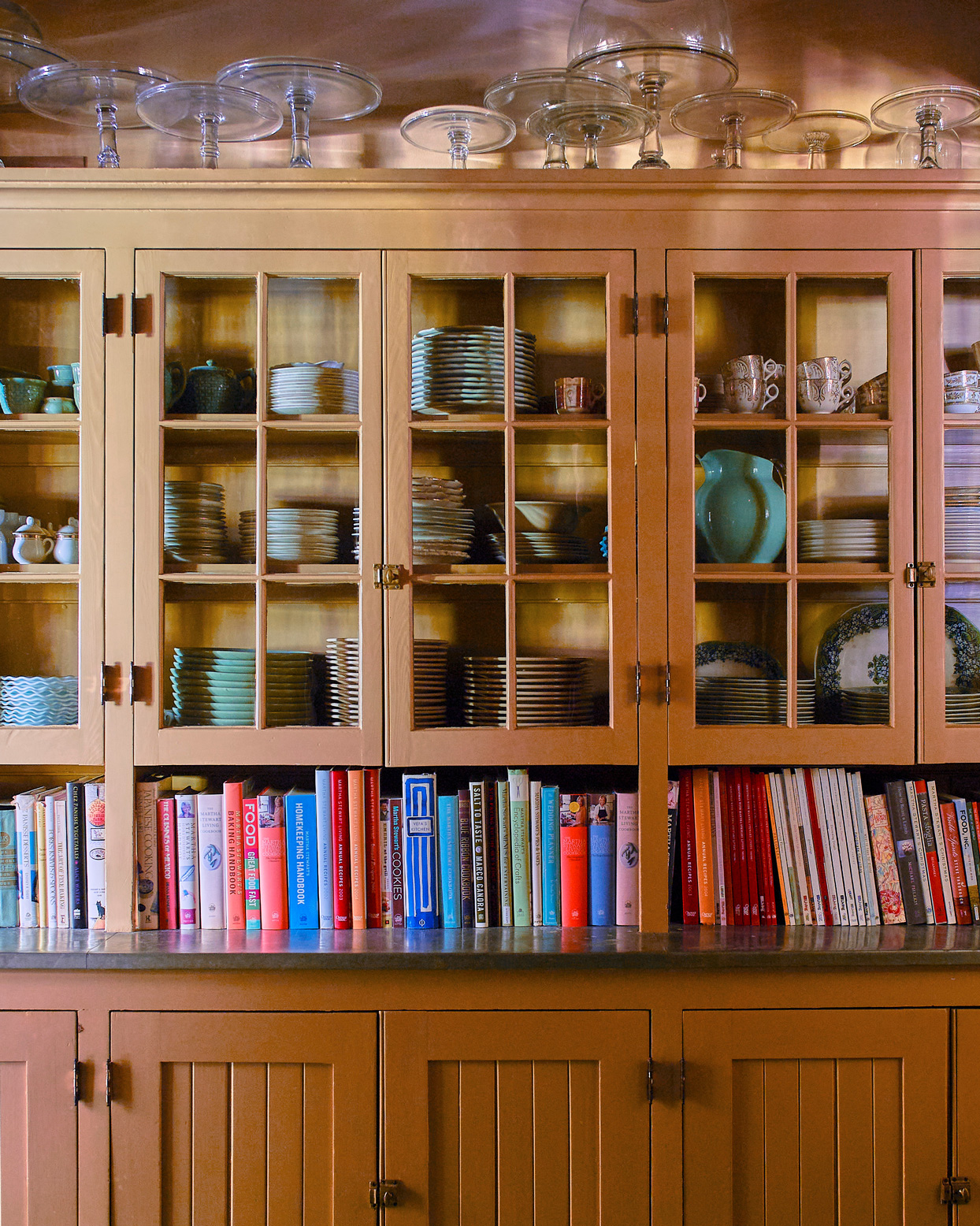dishes and cookbooks line cupboards