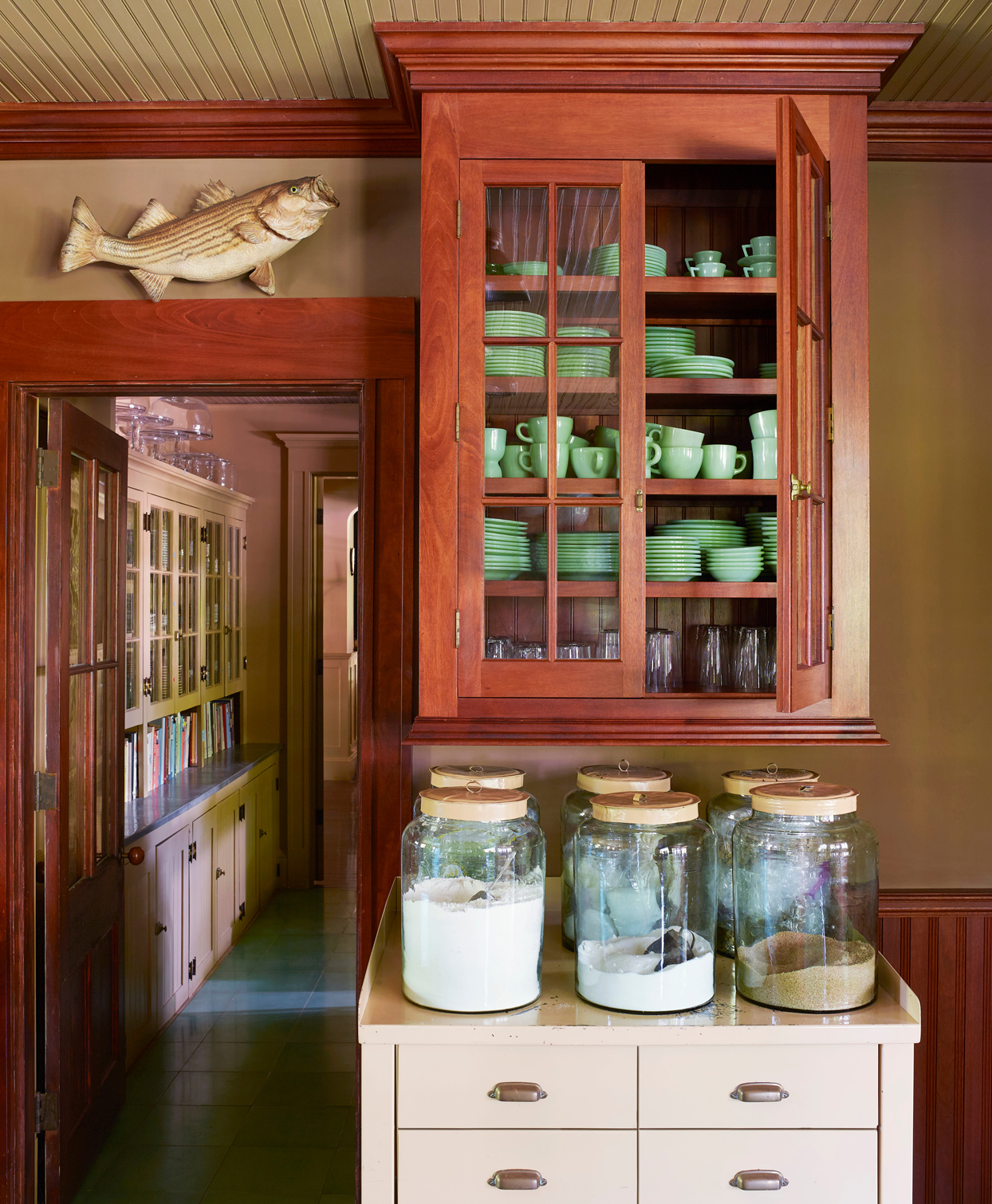 jadeite dishes fill a hanging mahogany cabinet