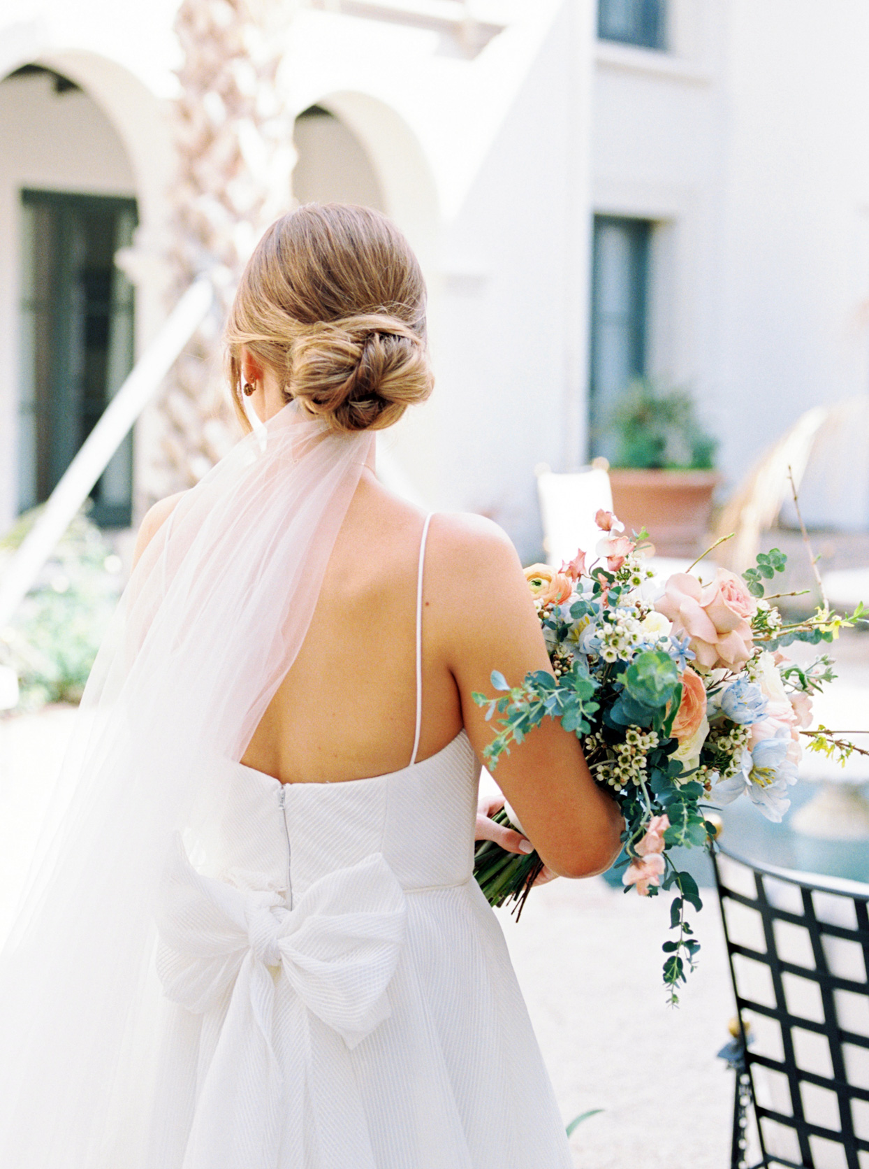 bride holding flowers showing bow on back of dress