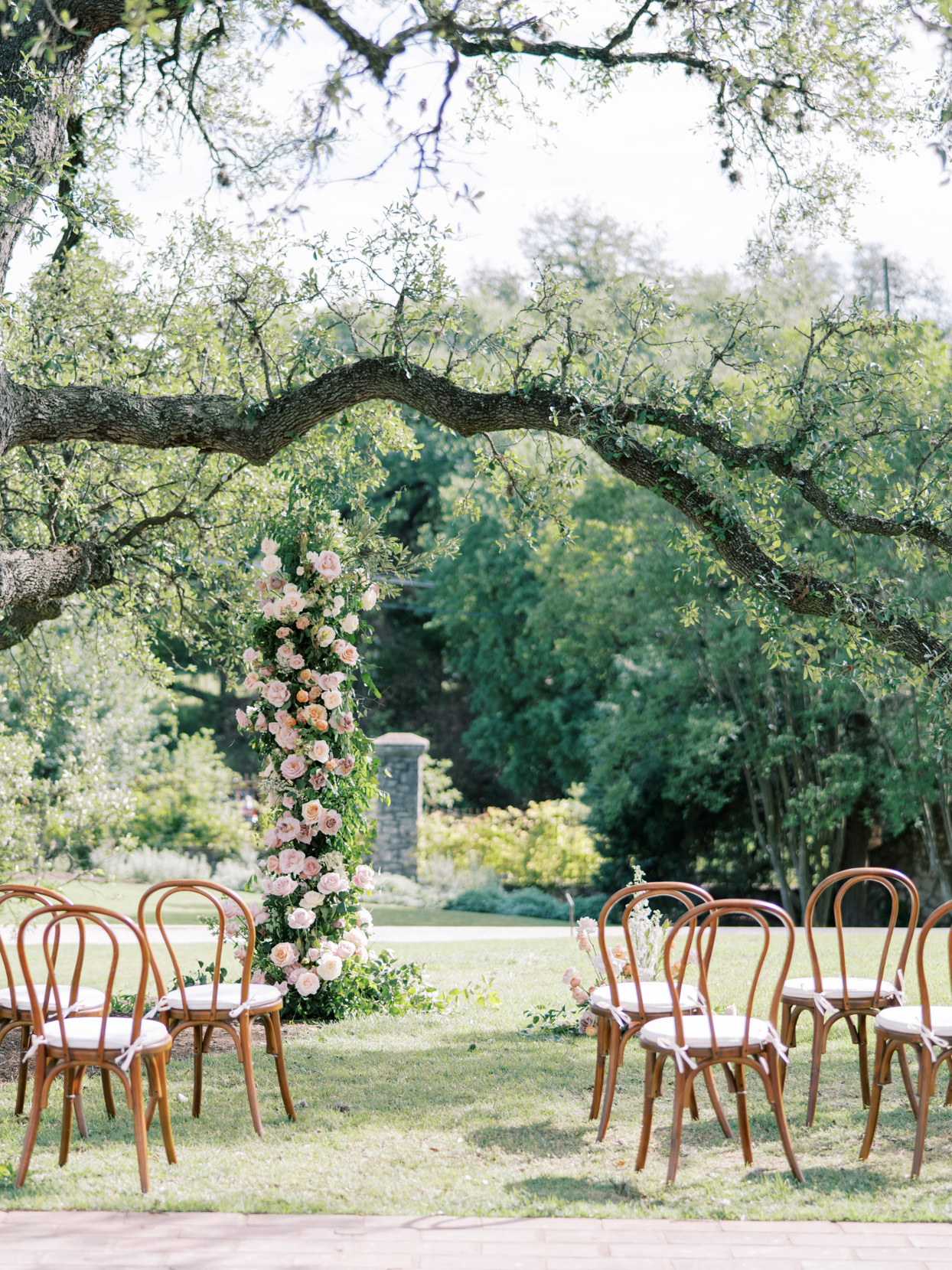 outdoor wedding ceremony location with wooden chairs and floral arch