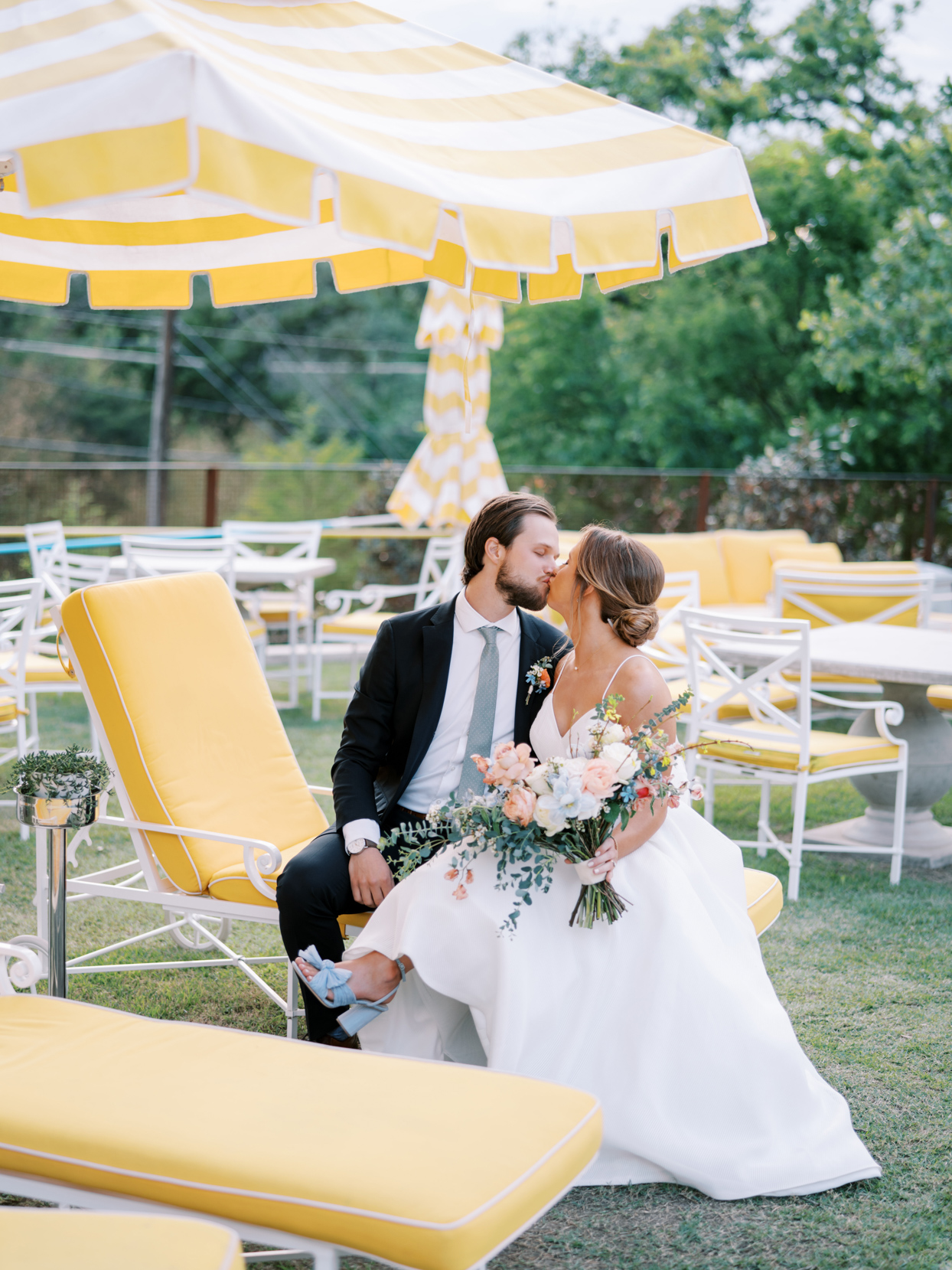 couple kissing on yellow patio lounge chairs