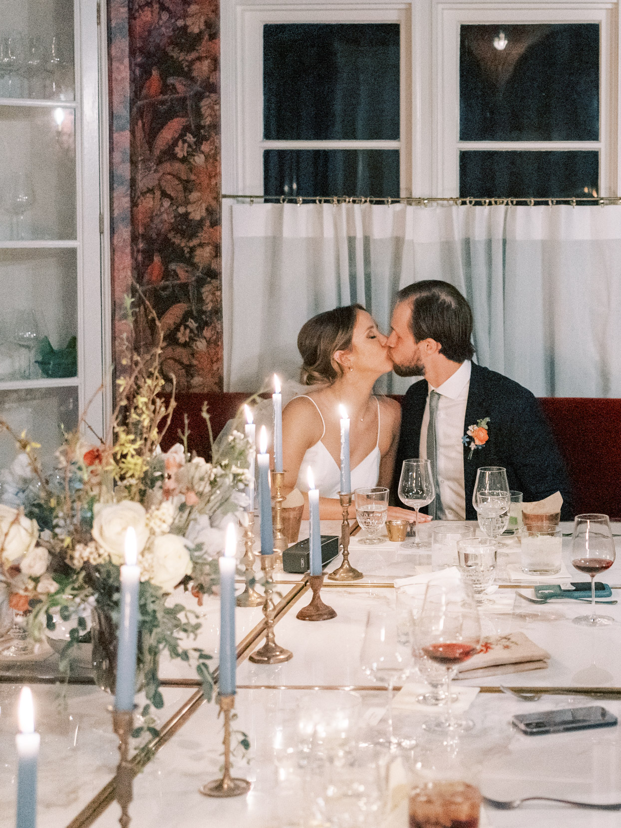 couple kissing at wedding reception table