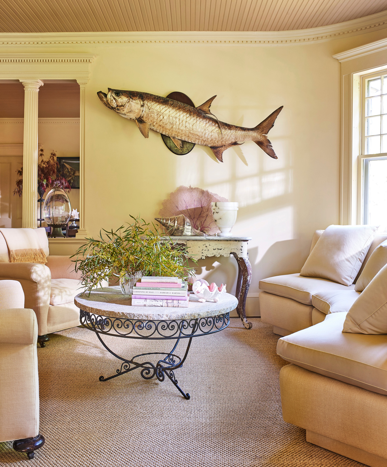 living room with curved linen sofa and taxidermy fish