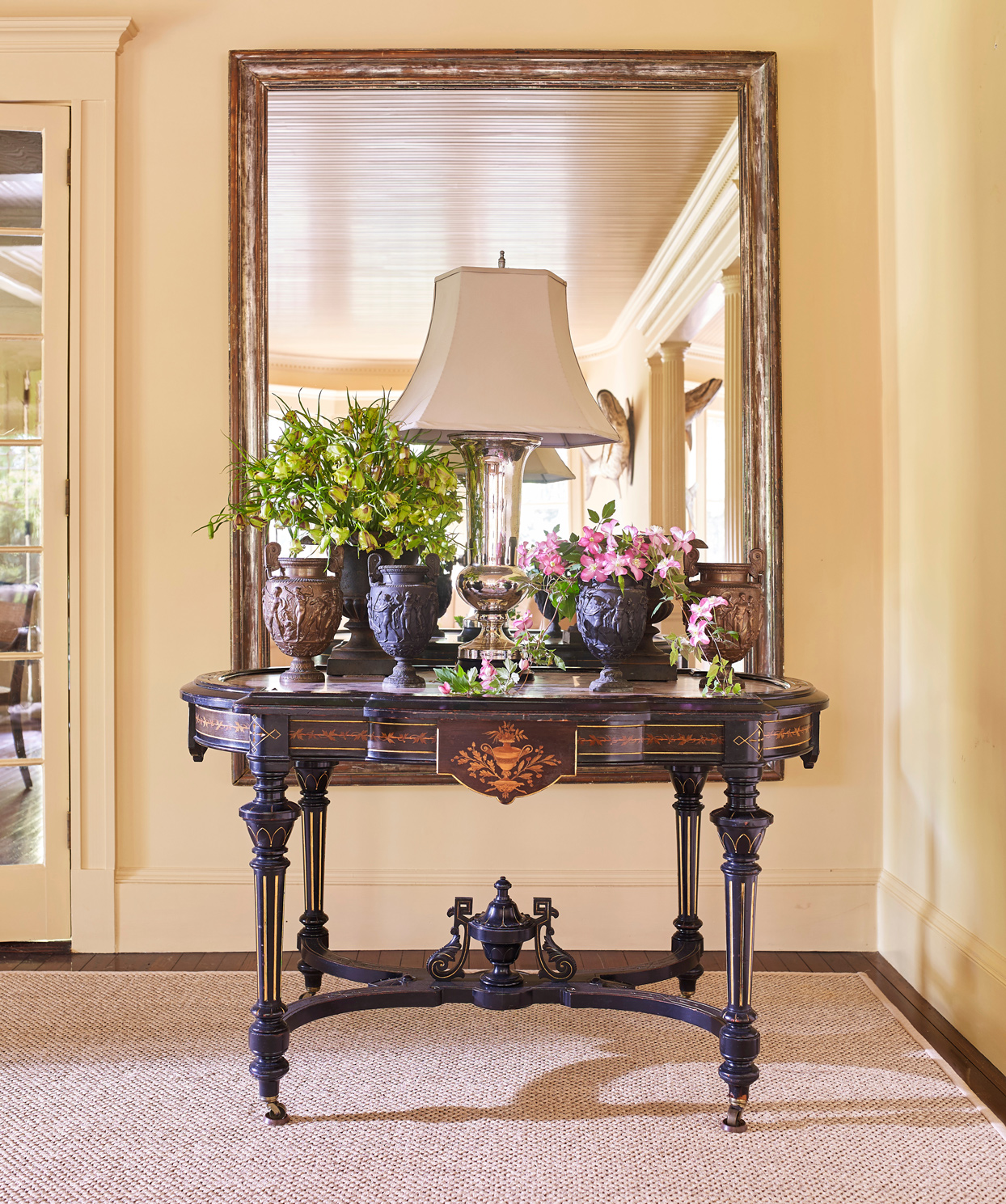 gilt-framed mirror hangs above aesthetic movement table with pink-marble top