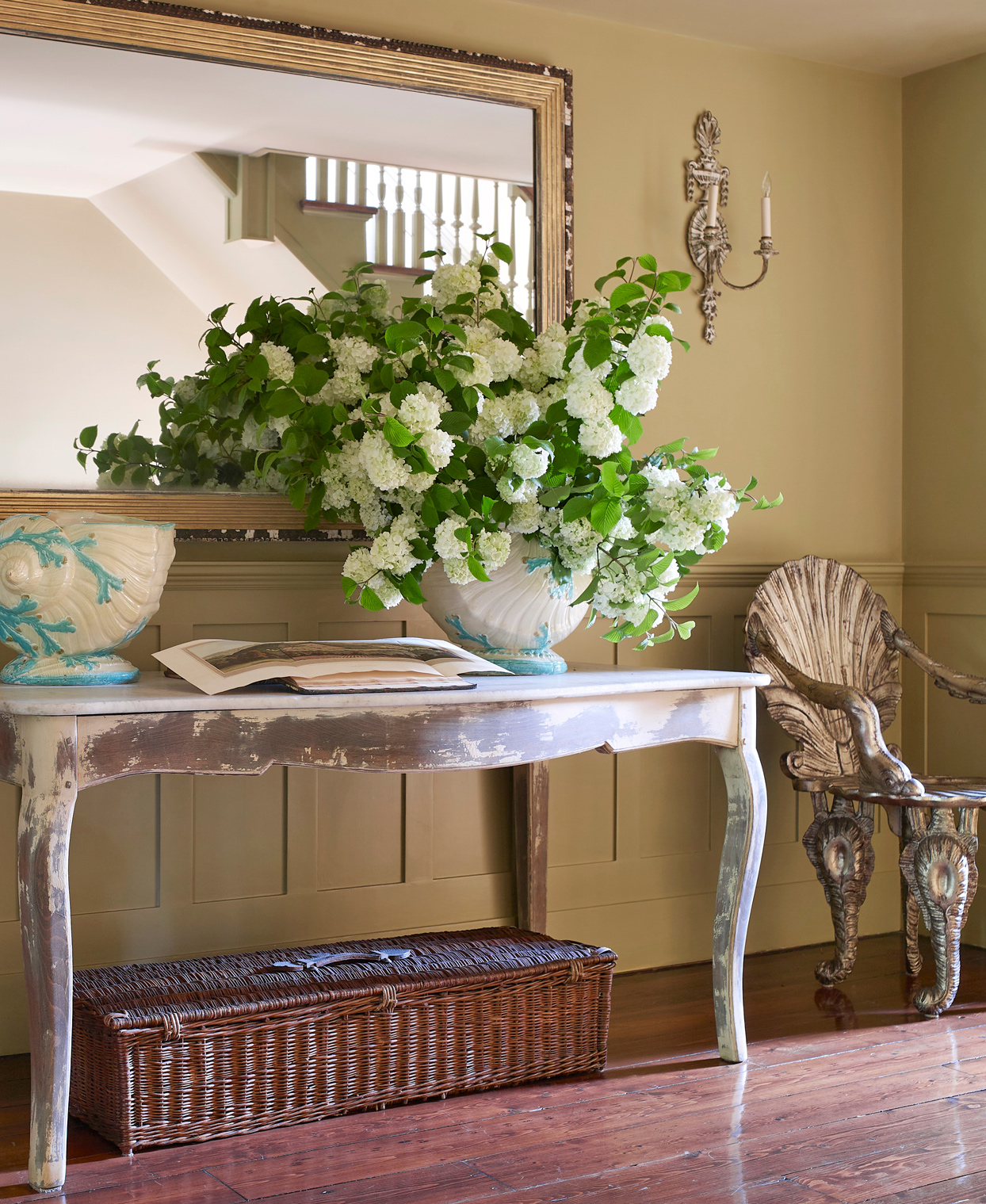 venetian-style shell chairs flank an antique swedish table
