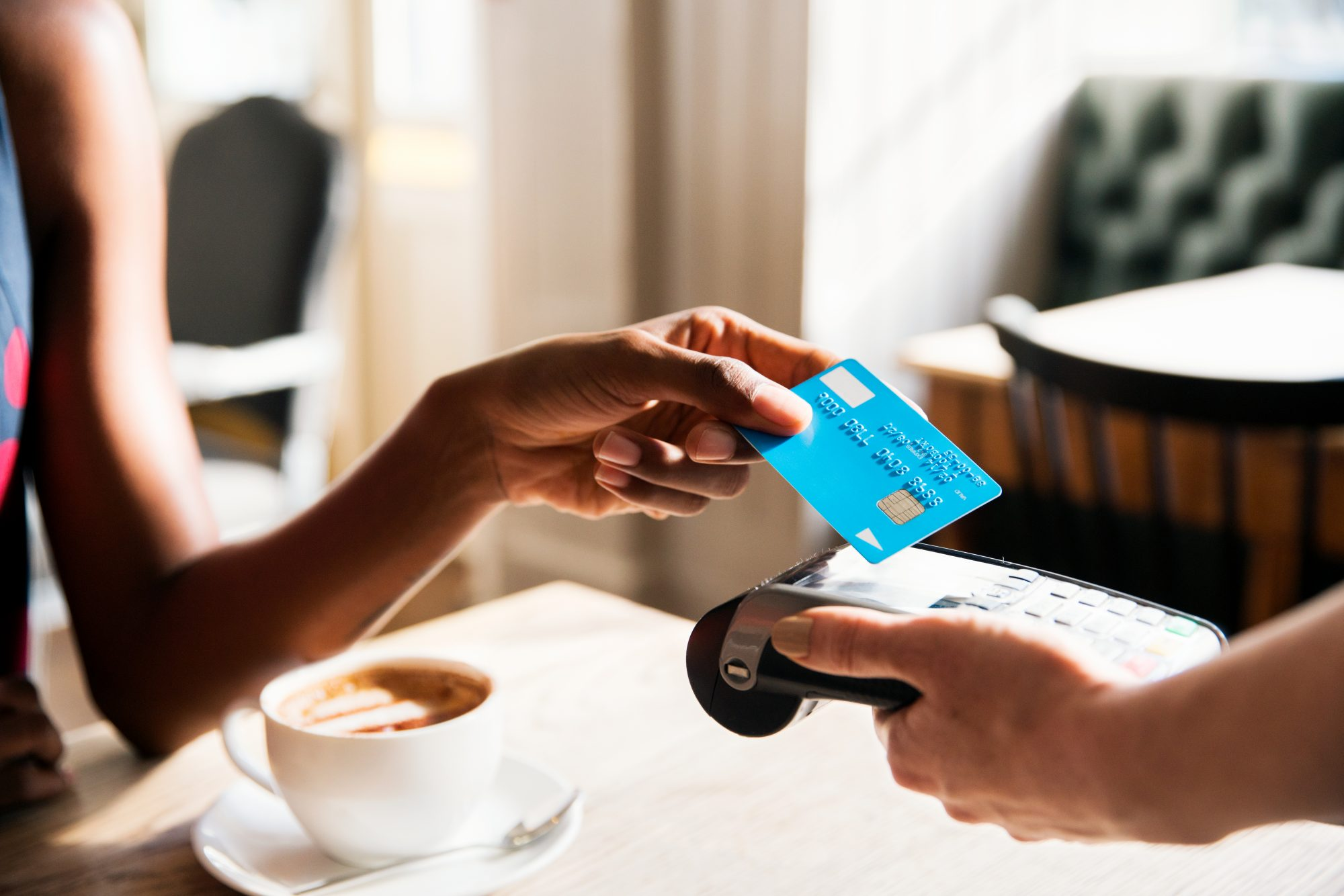 woman using credit card to buy coffee
