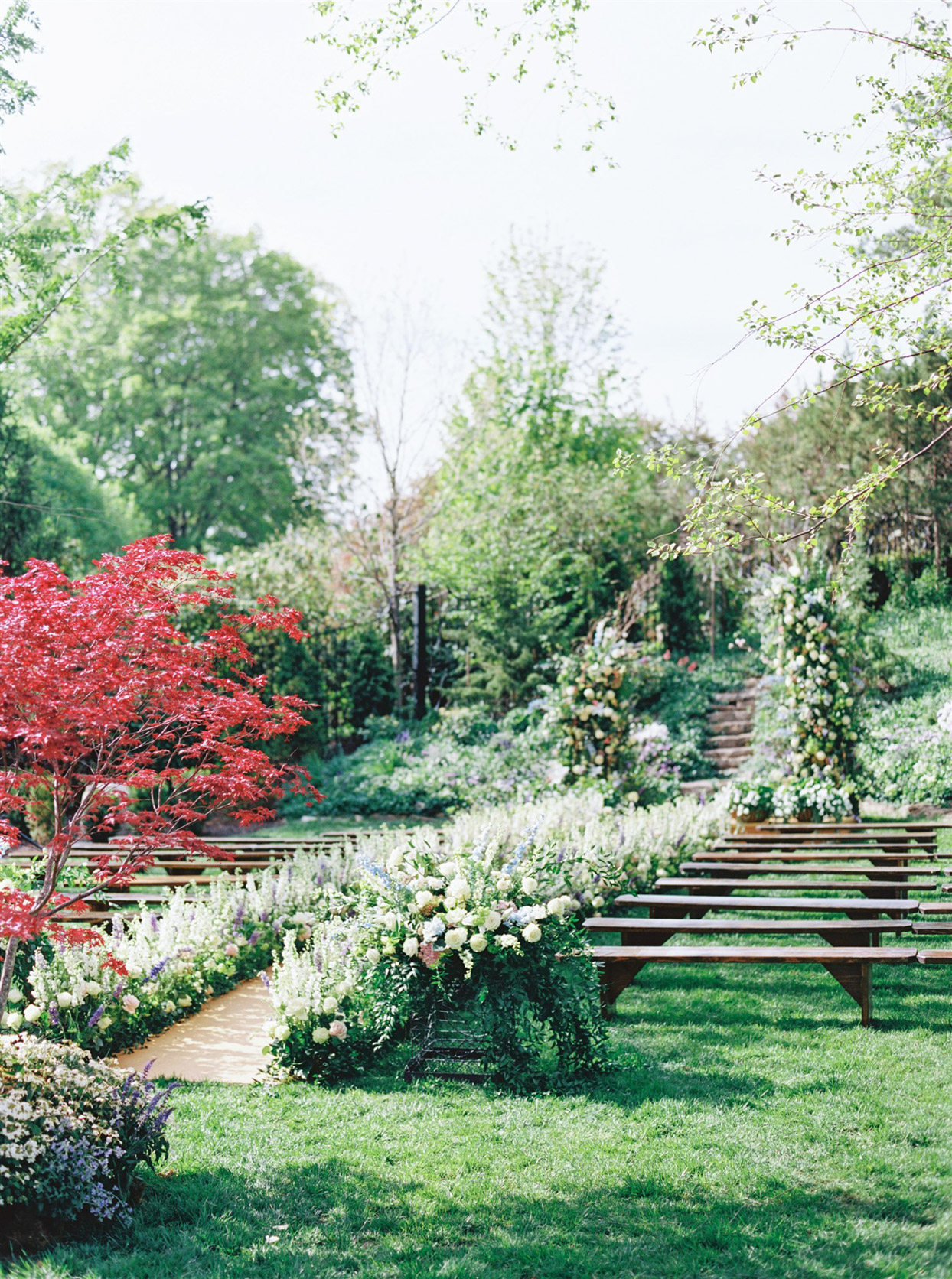 garden wedding ceremony with wooden bench seating
