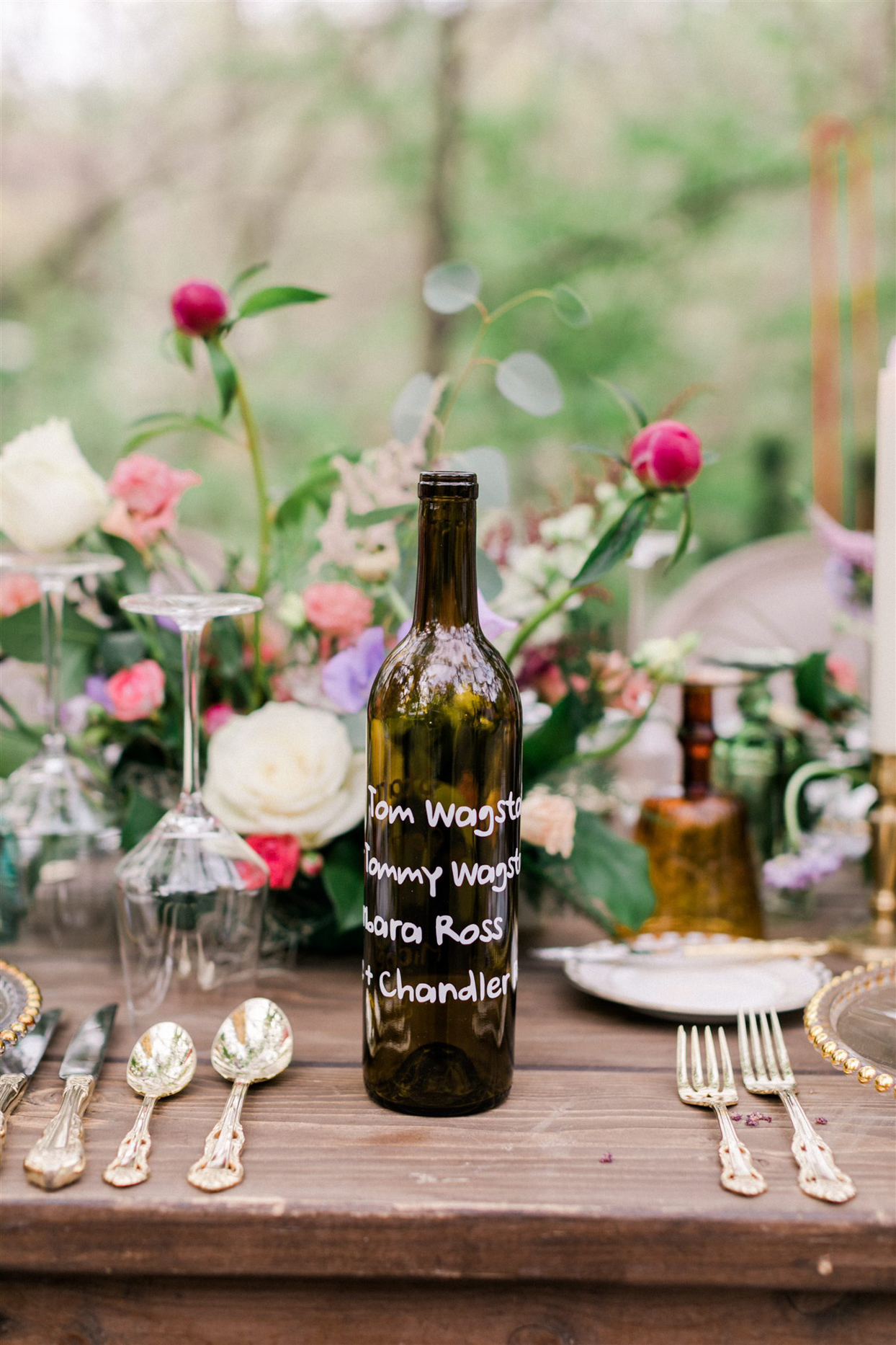 wedding table seating assignment on glass bottle centerpiece