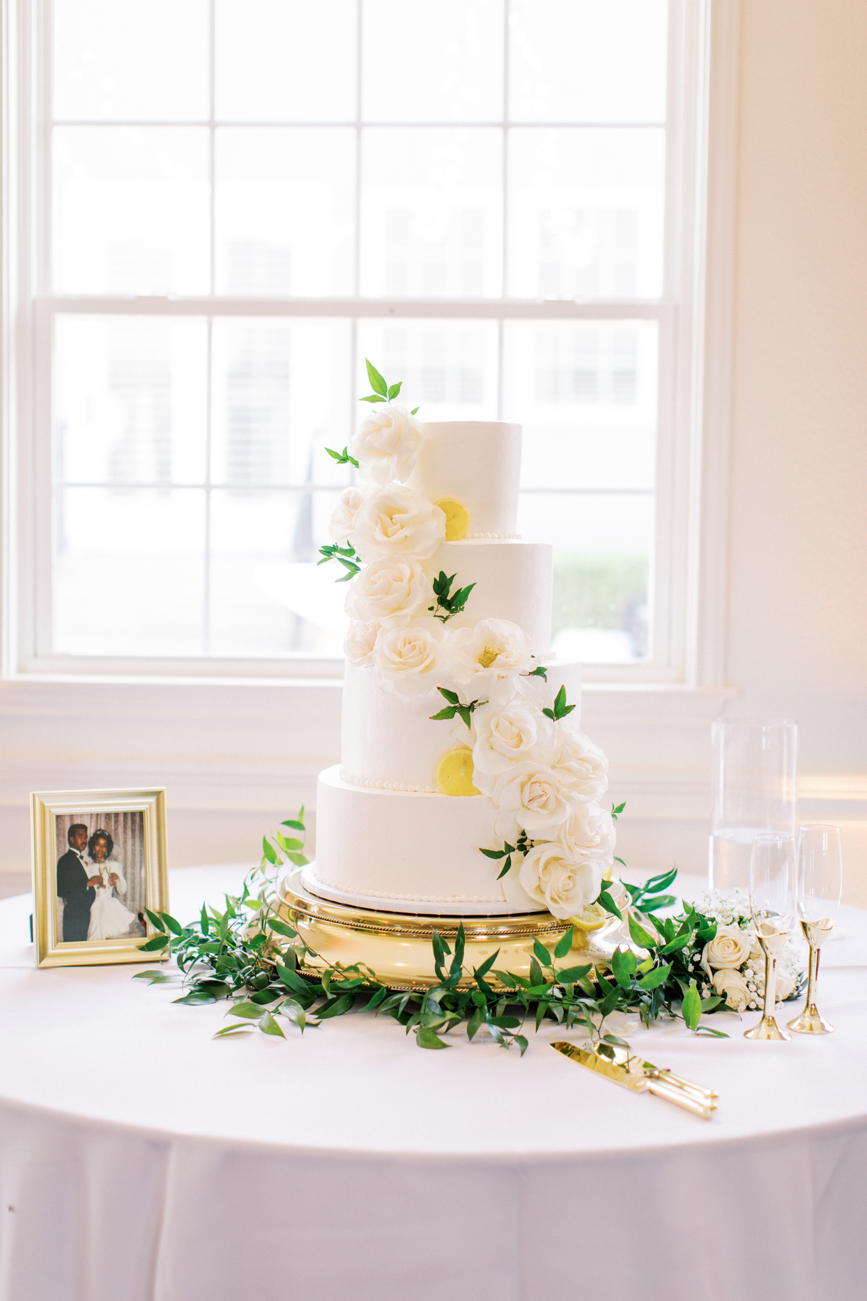 four tiered white frosted wedding cake with white rose accents