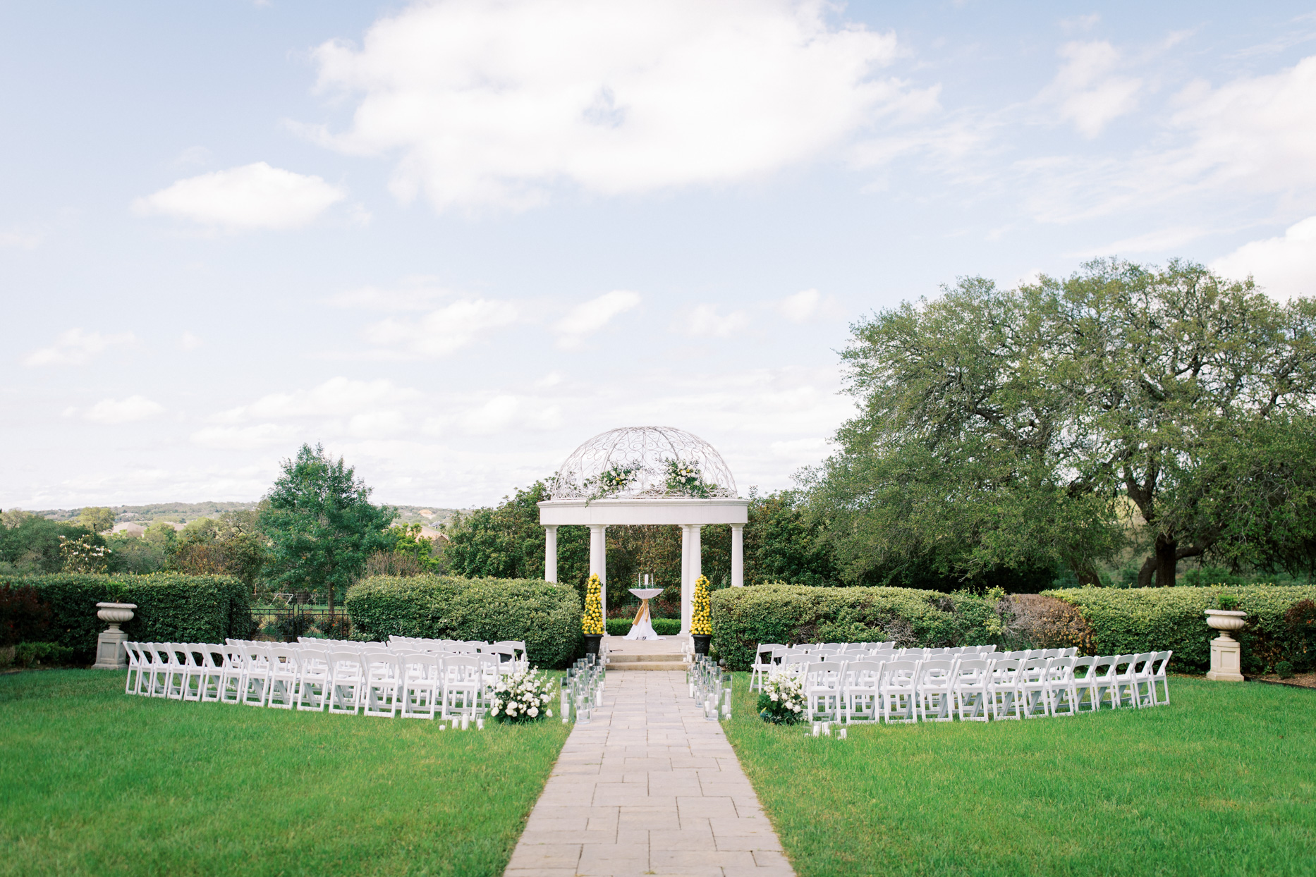 outdoor wedding ceremony set up with white chairs and floral decor