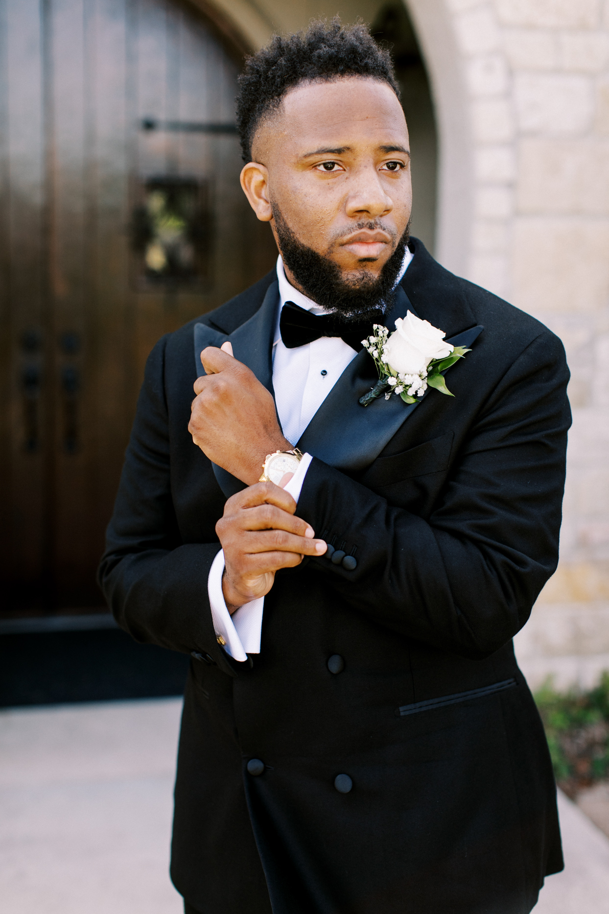 groom wearing classic black and white tux