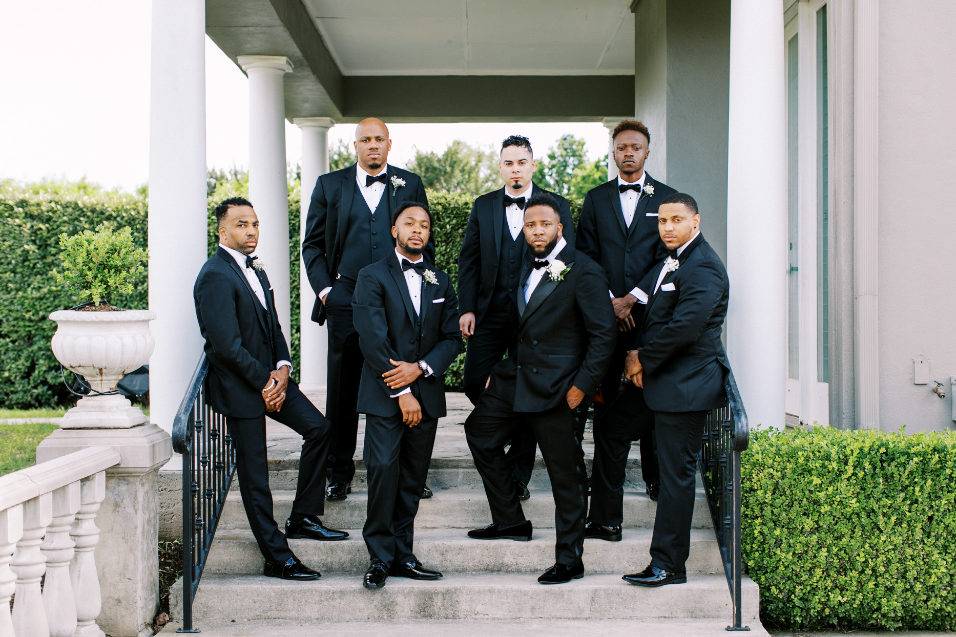 groom with groomsmen in classic black suits outside