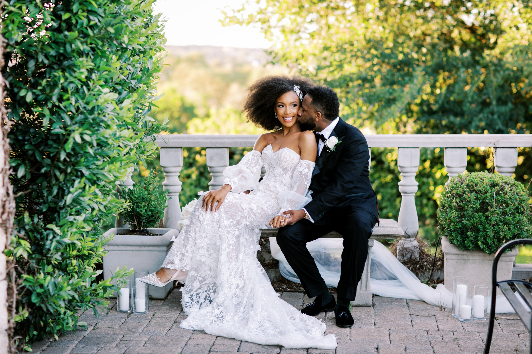 groom kisses bride on the cheek while sitting on outdoor bench