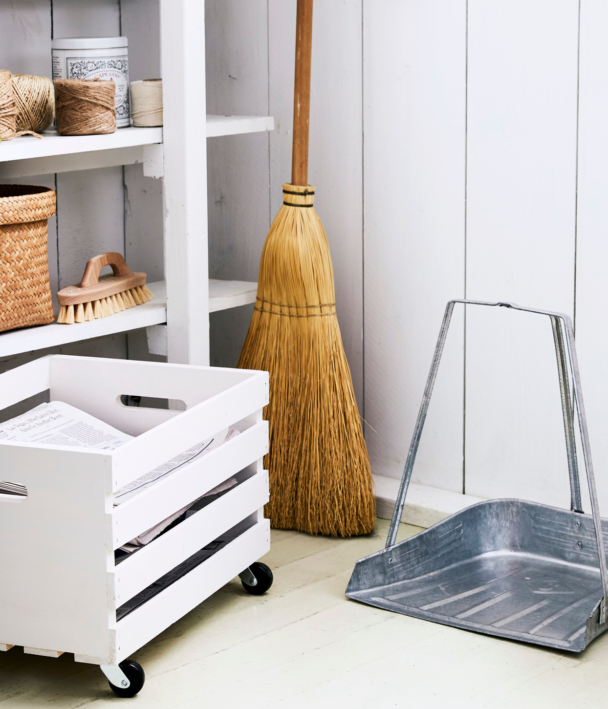 organized cleaning supply closet with broom and dustpan