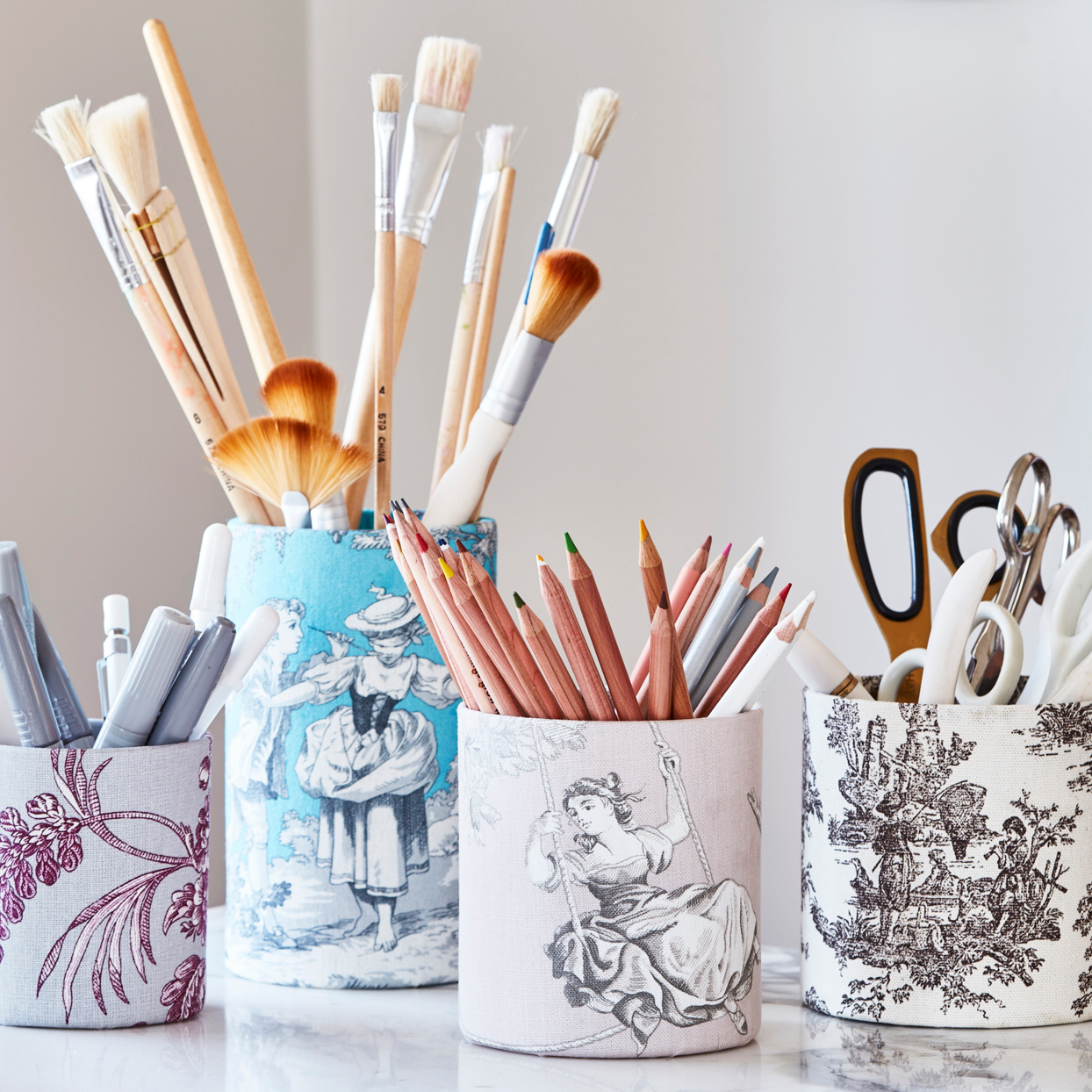 painted utensil cups with paint brushes and colored pencils