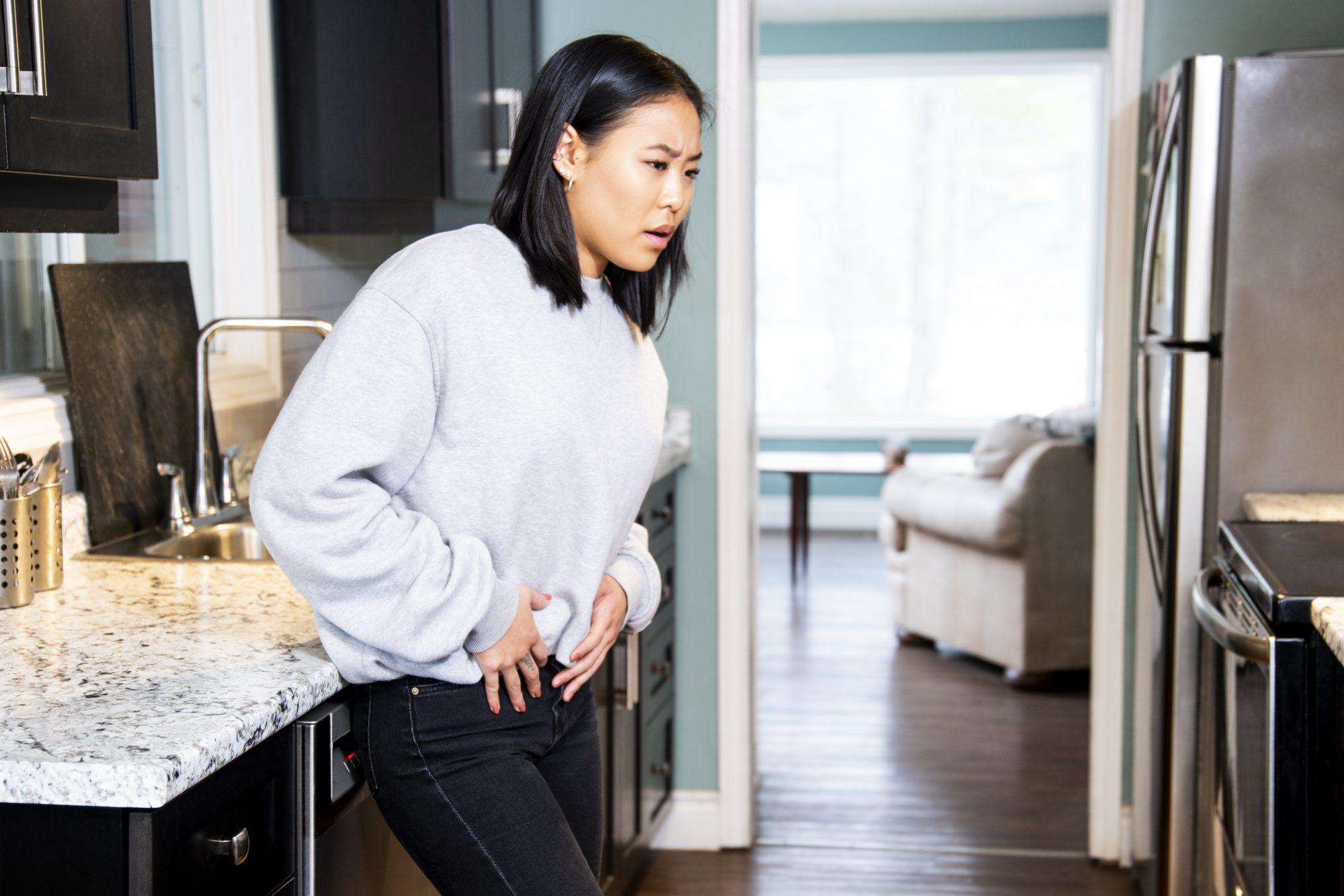 woman touching stomach standing in kitchen