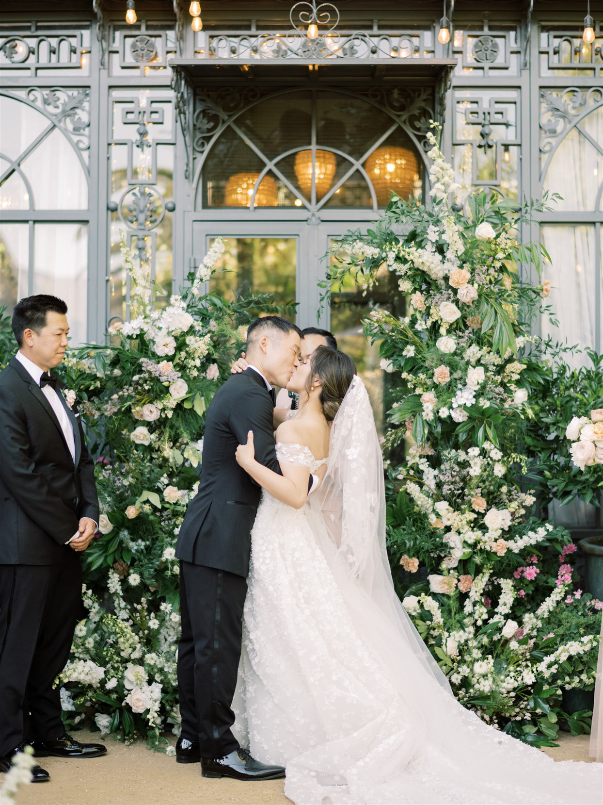 bride and groom share a kiss during wedding ceremony