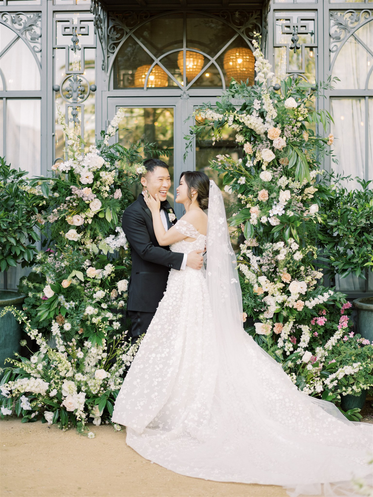 bride and groom smile amidst floral decor