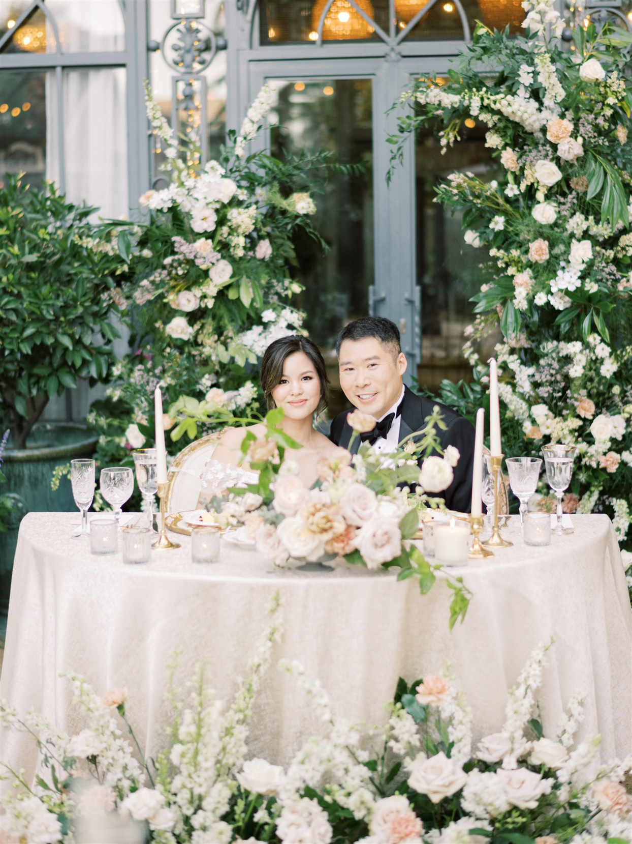 bride and groom smiling sitting at sweetheart table