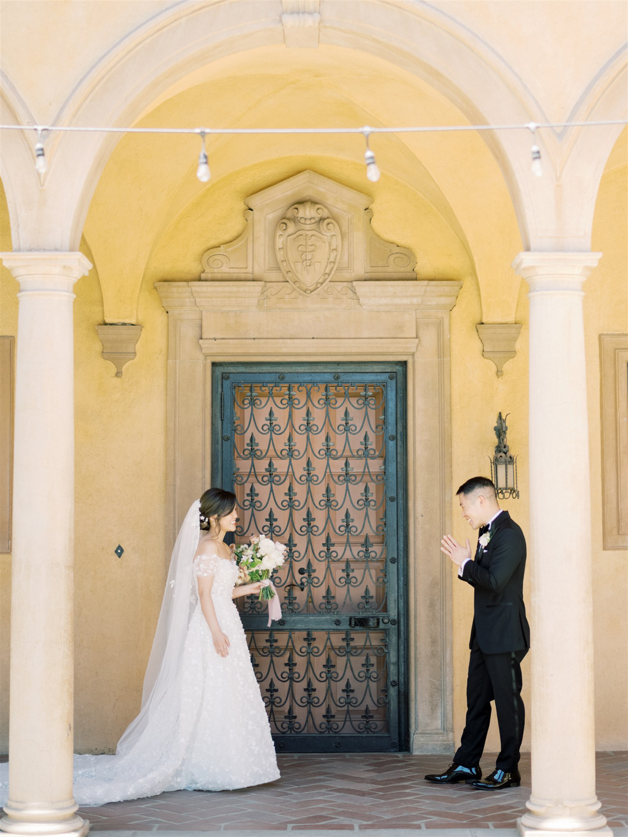 groom smiling at bride during first look outside