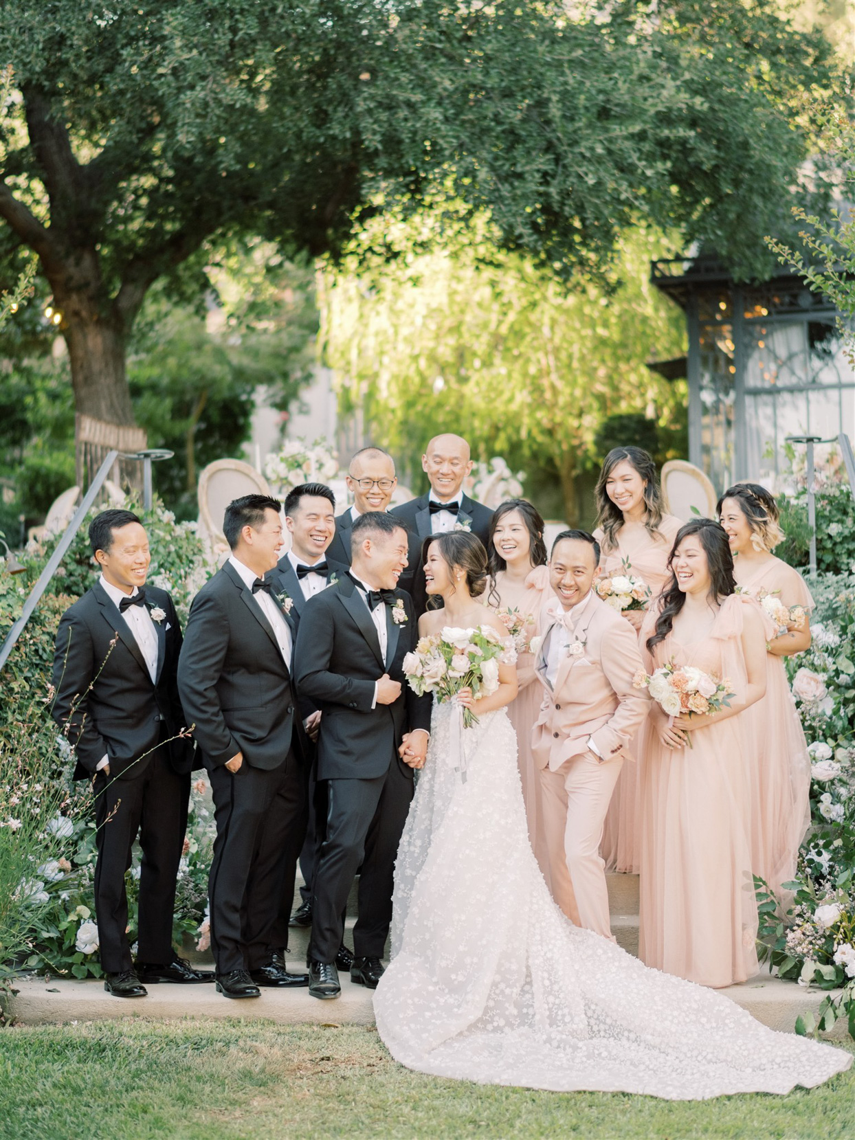 bride and groom surrounded by wedding party smiling outside