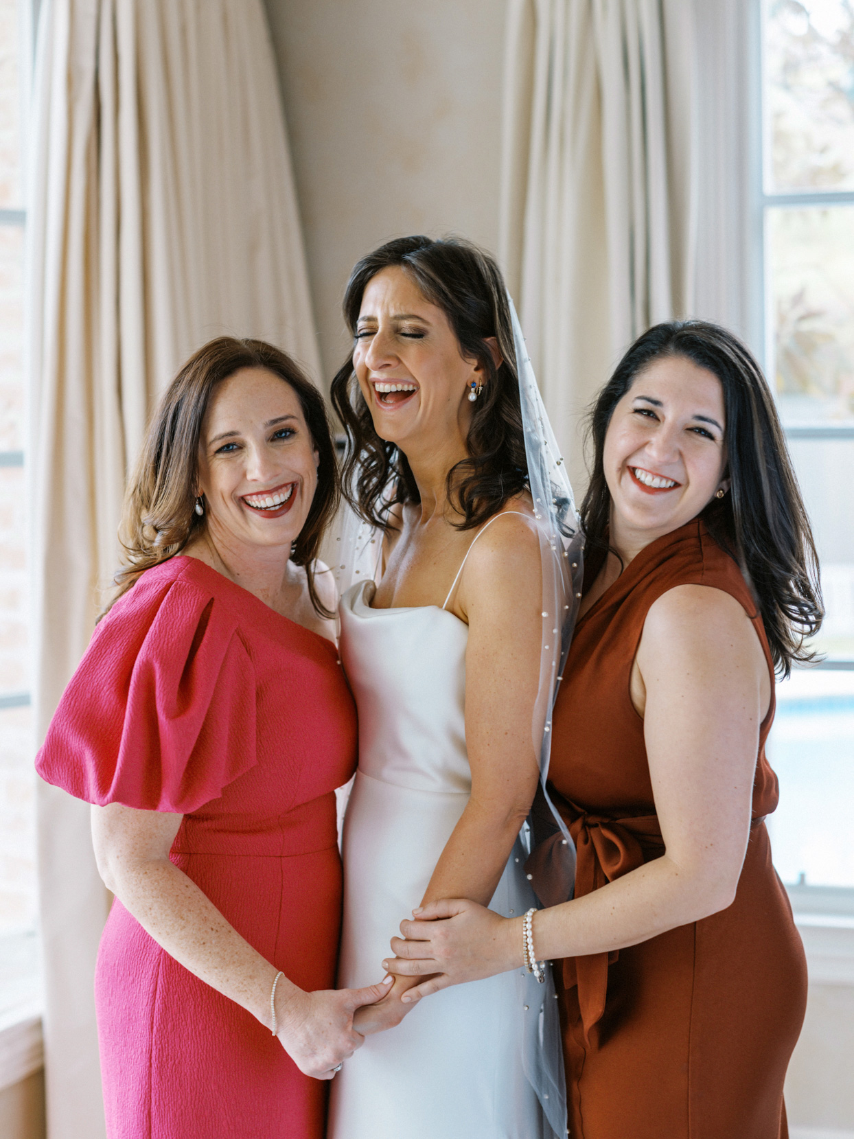 bride laughing and smiling with two bridesmaids