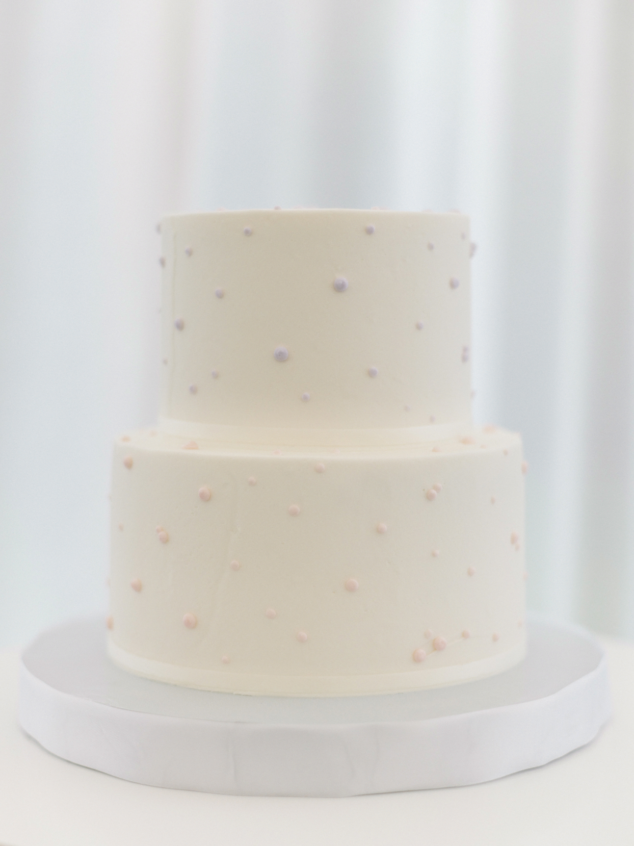 two tiered simplistic white frosted wedding cake