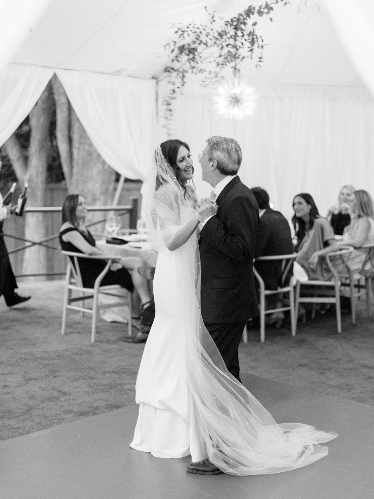 father daughter dance under white reception tent